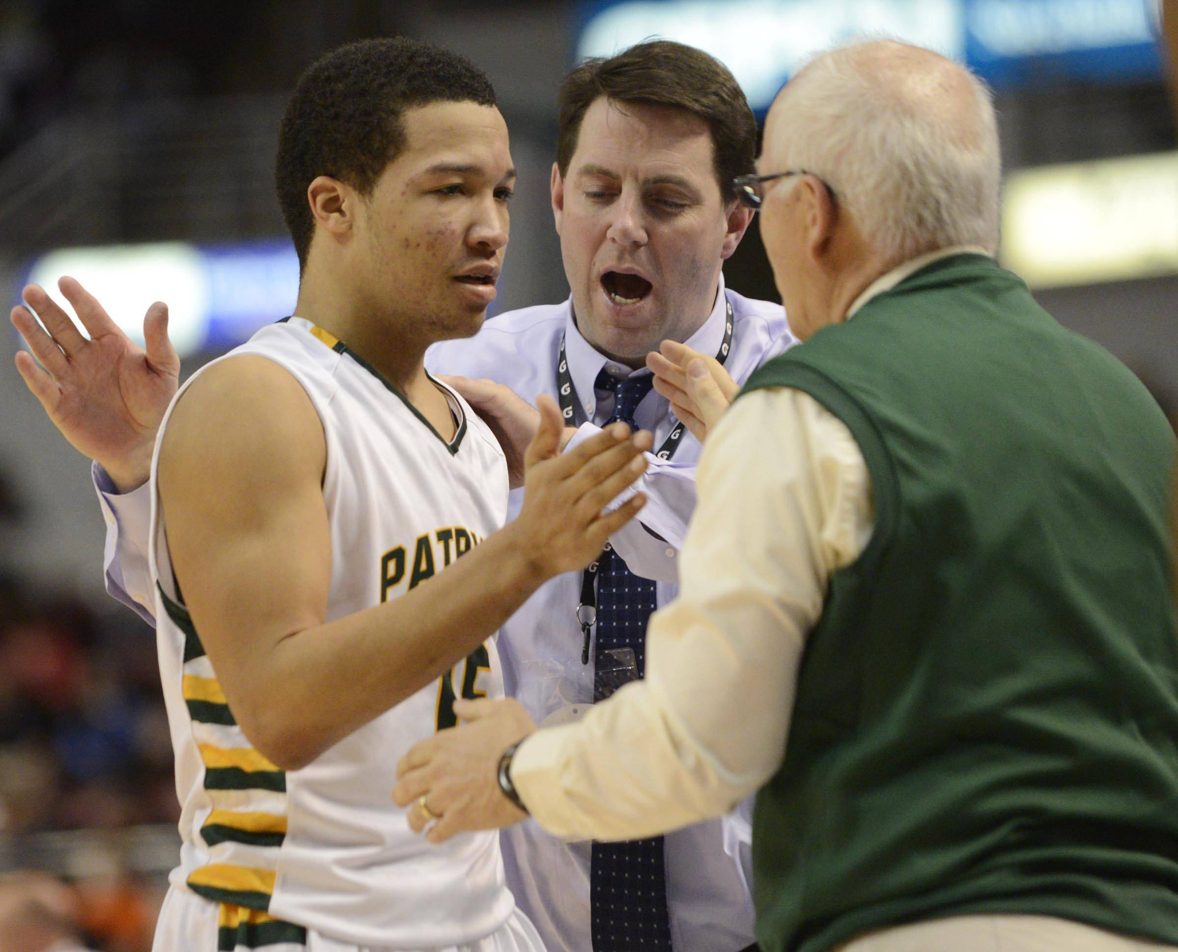 Stevenson's Jalen Brunson is met by his coaches as he leaves the game against Edwardsville in the Class 4A third-place game at Carver Arena in Peoria on Saturday.