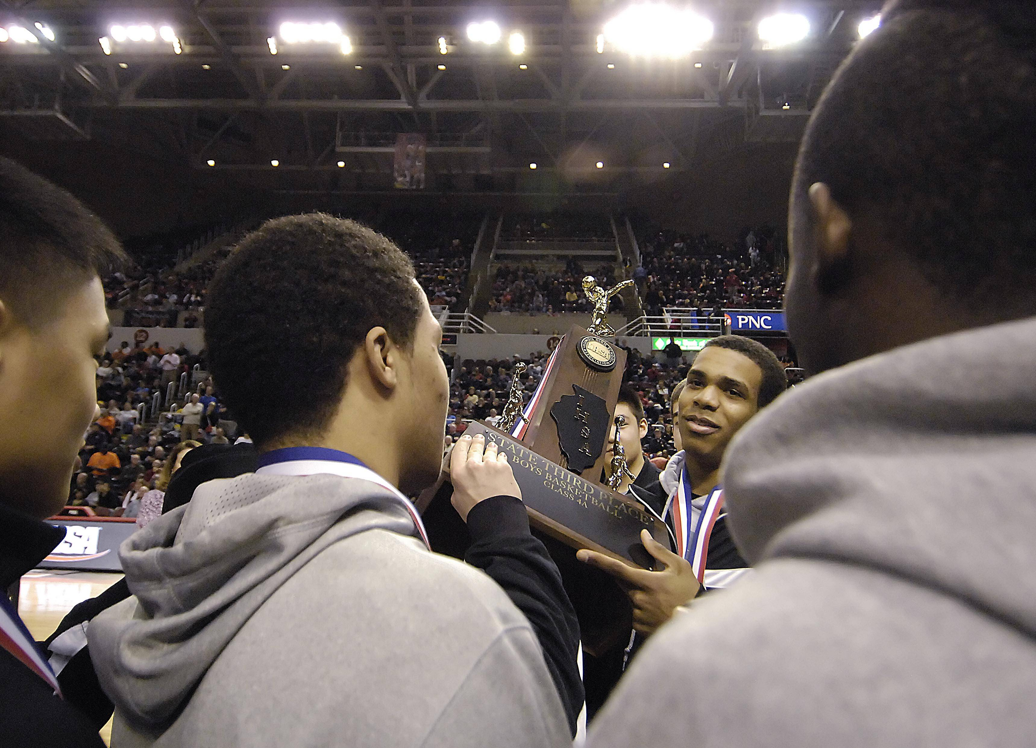 Stevenson's Connor Cashaw holds the third-place trophy with his teammates after the Patriots beat Edwardsville 70-63 in the Class 4A third-place game at Carver Arena.