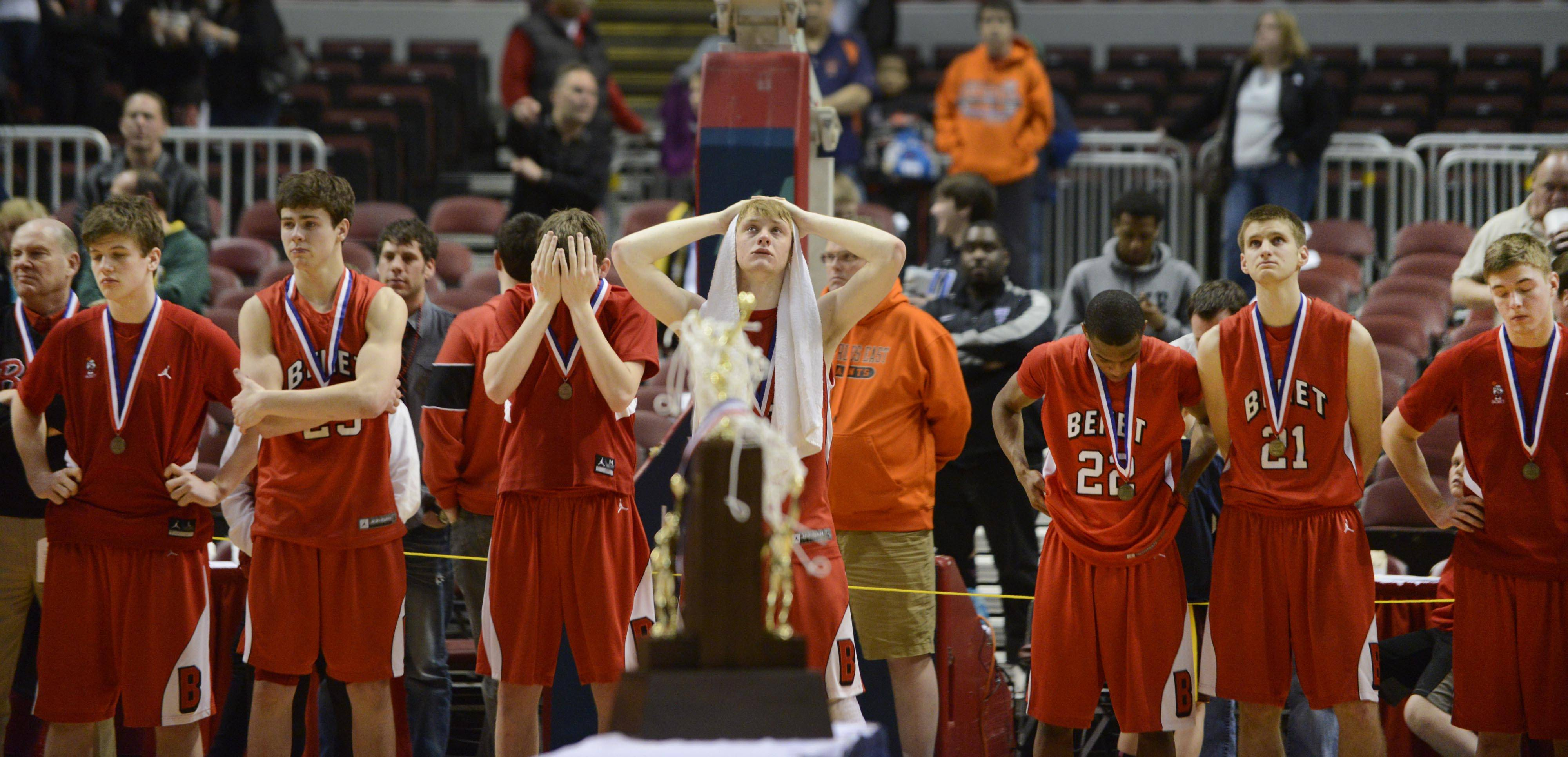 Benet Academy's Liam Nelligan holds a towel on his head as he waits with his teammates for their second place trophy after losing to Whitney Young in the Class 4A state championship game at Carver Arena in Peoria Saturday.