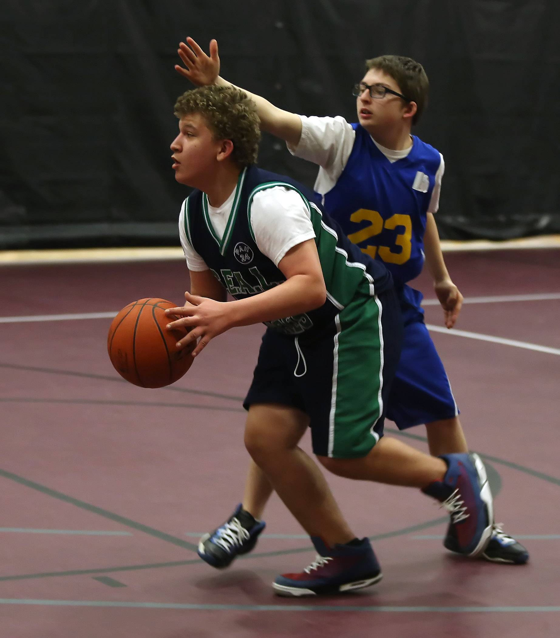 SEAL North school player Bob Vitello of Lombard dribbles past Cove School player Jackson Kozeny of Northbrook during Sunday's Chicago Area Alternative Education League basketball tournament in Arlington Heights.