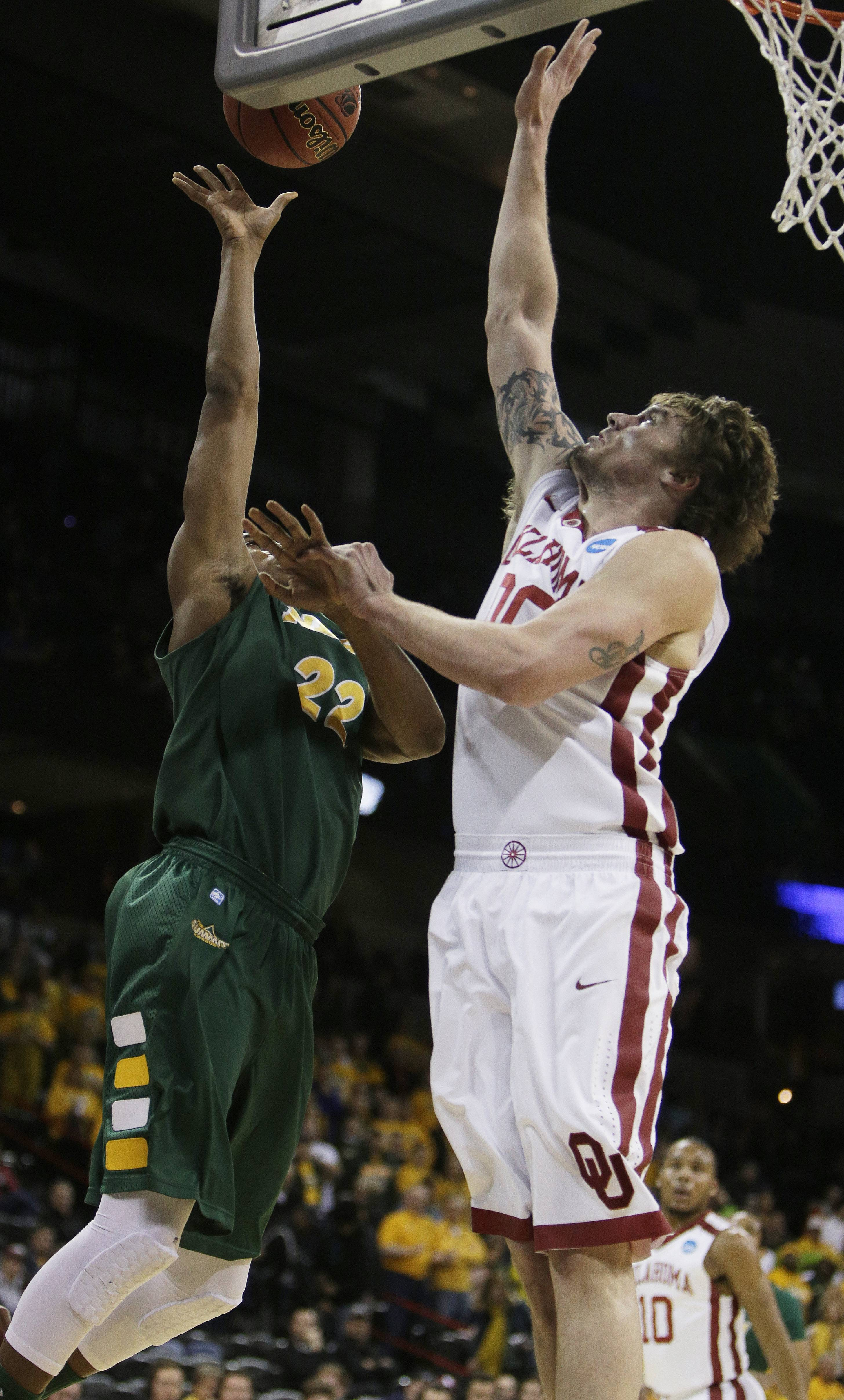 North Dakota State's Kory Brown (22), an Elgin High graduate, shoots as Oklahoma's Ryan Spangler defends during a second-round game of the NCAA Tournament in Spokane, Wash., last week.