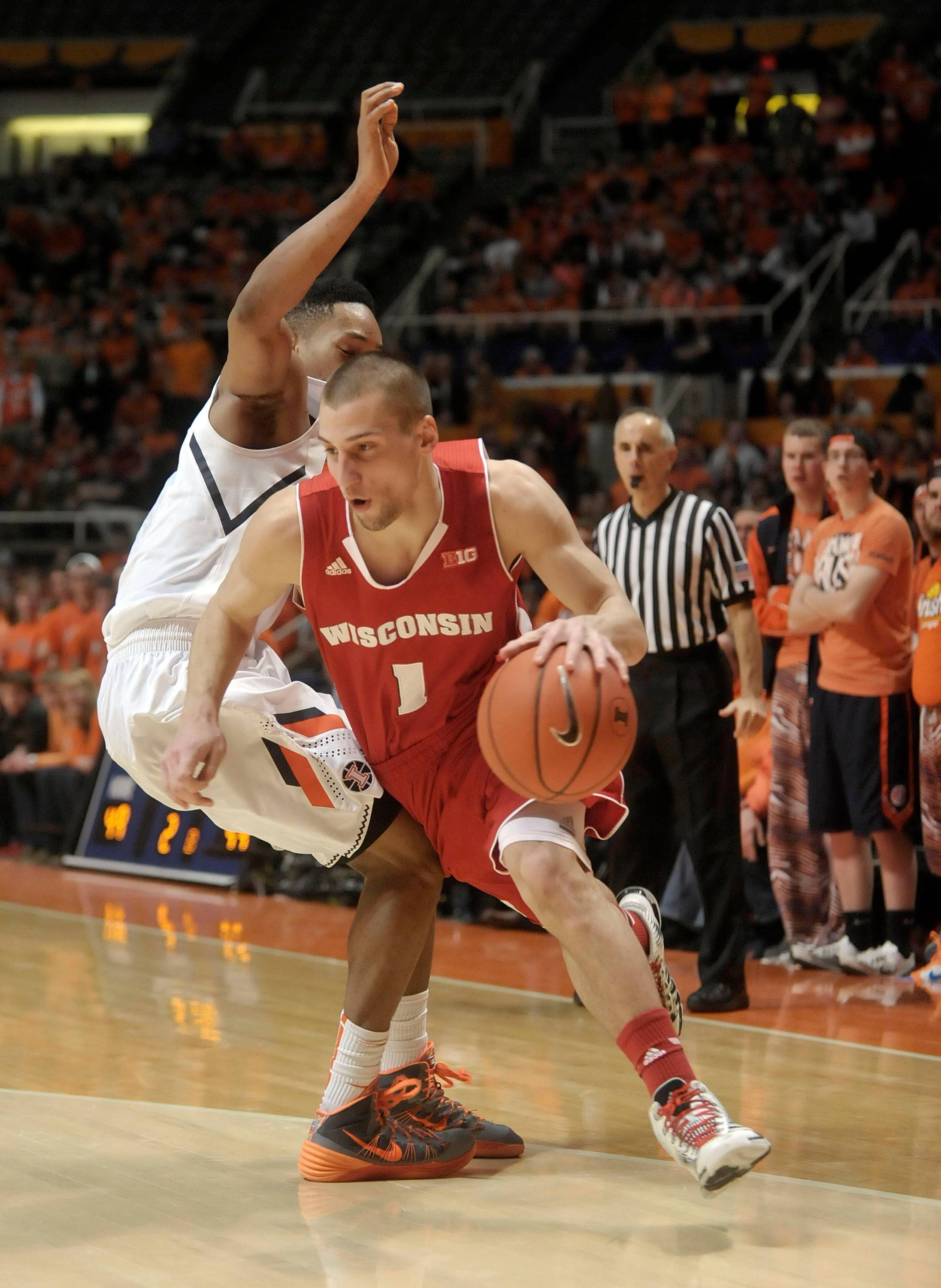 Wisconsin guard Ben Brust drives around Illinois' Joseph Bertrand on Feb. 4 in Champaign. Wisconsin won 75-63.