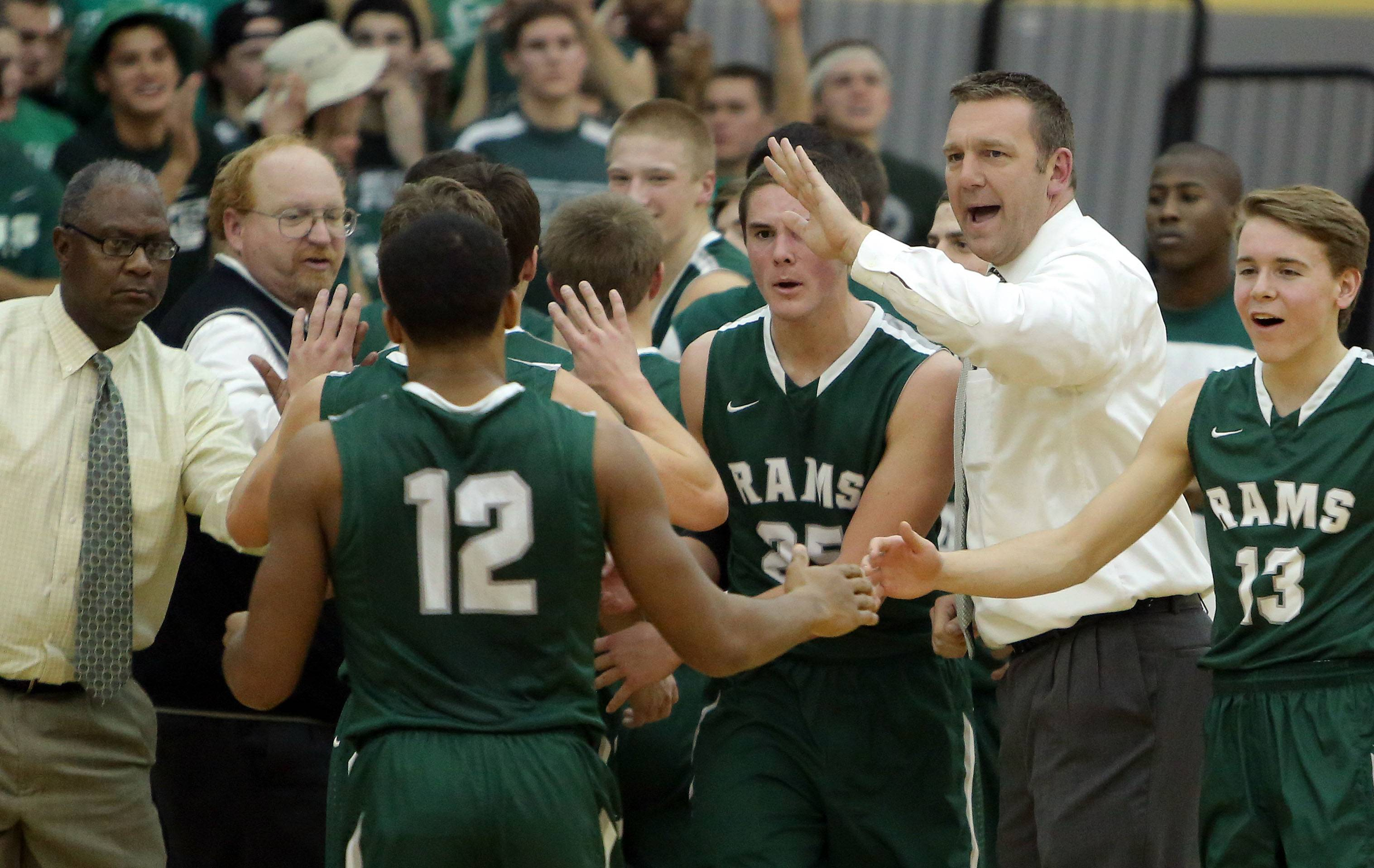 Grayslake Central's Brian Moe, right, encourages his basketball team during a timeout against Grayslake North.