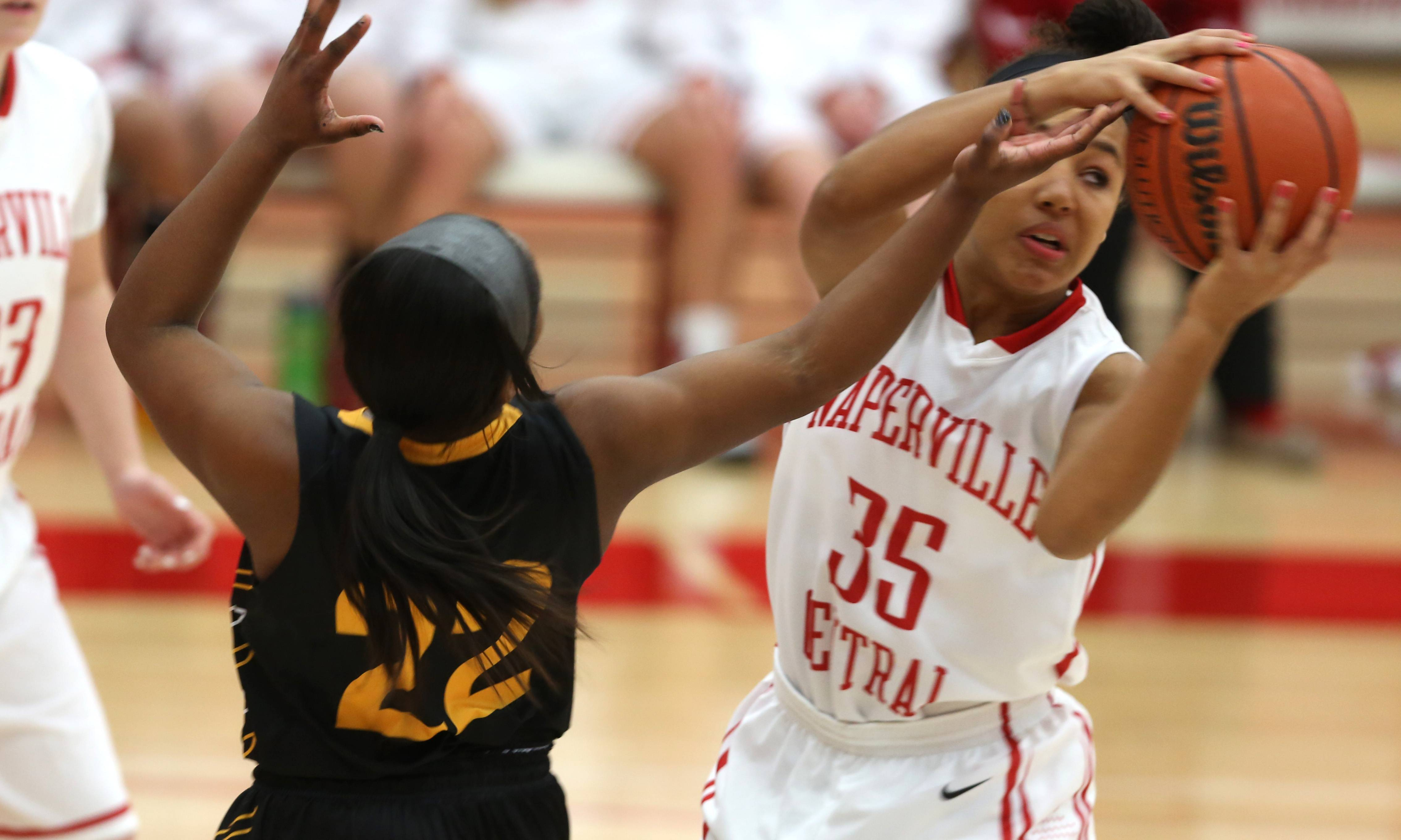 Naperville Central's Casey Smith, right, swipes the ball past Metea Valley's Taseandra Parker during the 2014 Naperville Central Tip-Off Tournament.