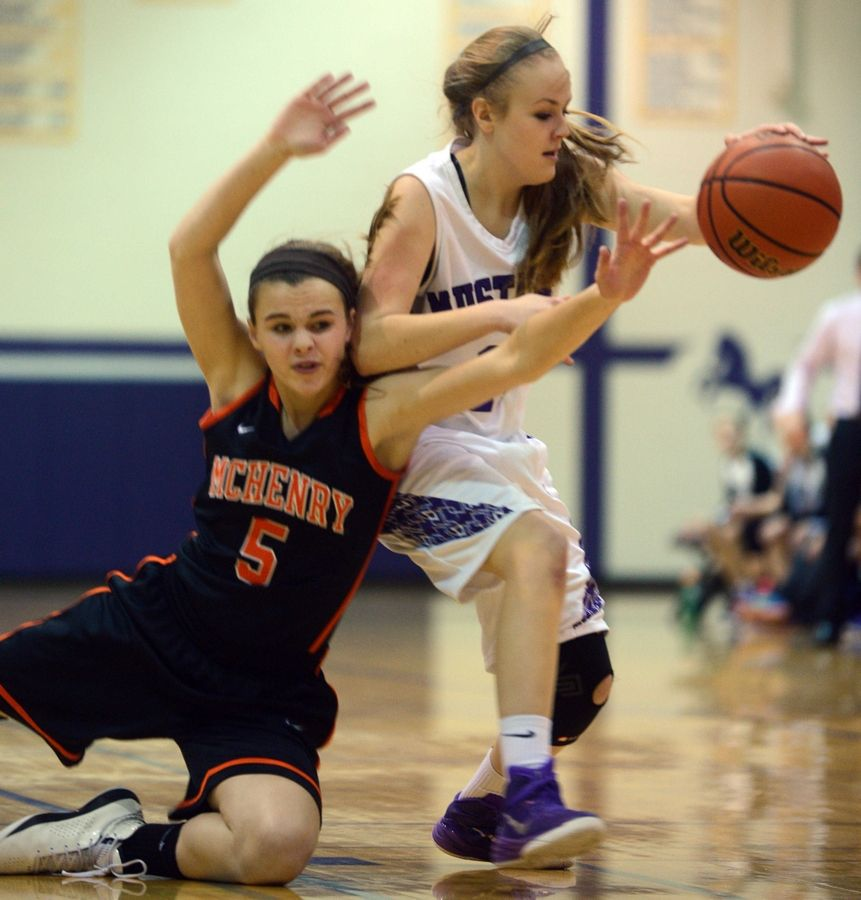 Rolling Meadows' Kelsey Nallon, right, battles McHenry's Kaleigh Johnson, left, at Rolling Meadows on Monday.