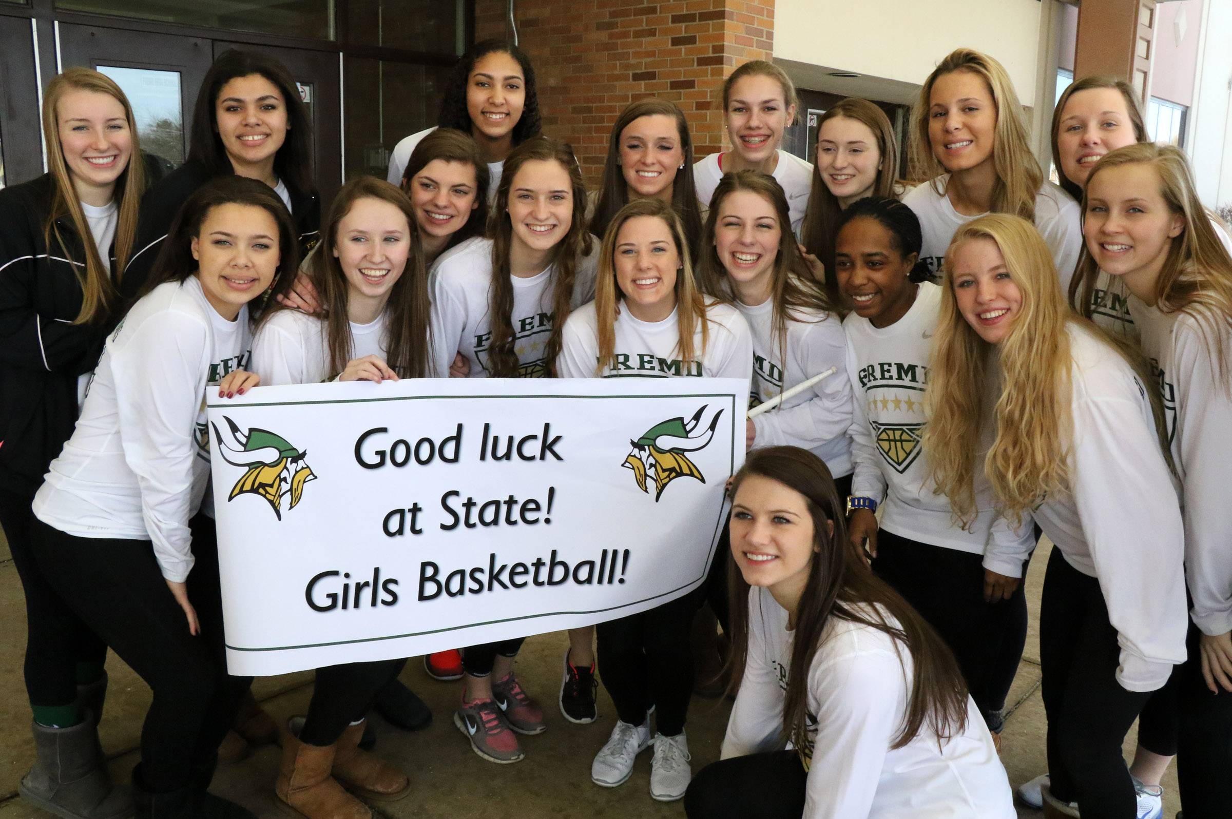 The Fremd High School girls' basketball team poses outside the Palatine school after they got a big send-off to the state tournament on Wednesday. The girls depart on Thursday.