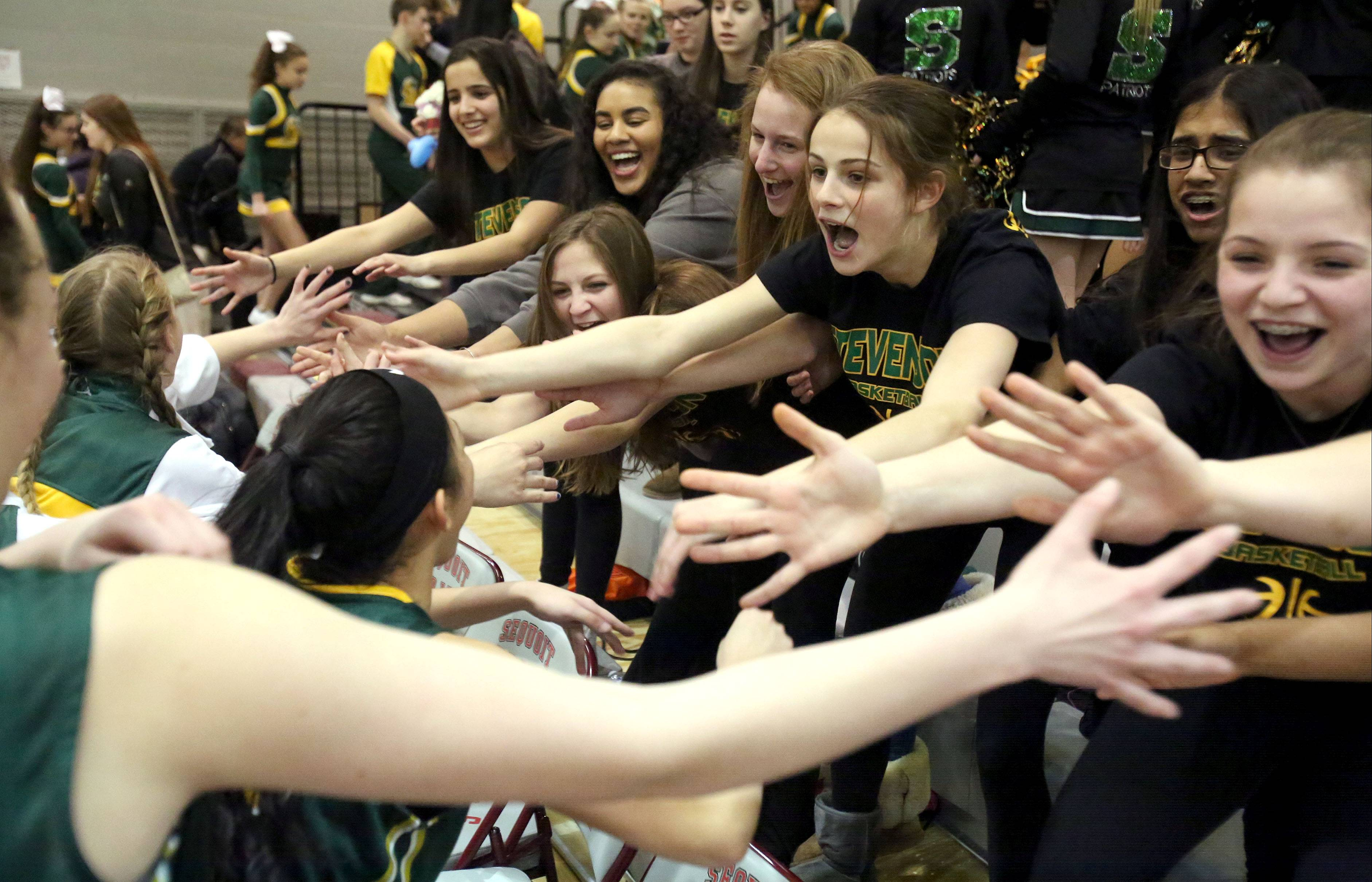 Stevenson fans high-five their team after the Patriots topped Antioch in the NSC title game Wednesday night at Antioch.