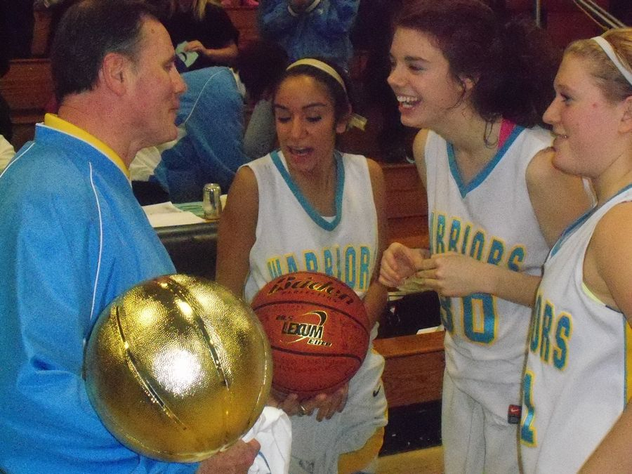 Maine West coach Derril Kipp receives congratulations from some of his players after winning his 700th career game.