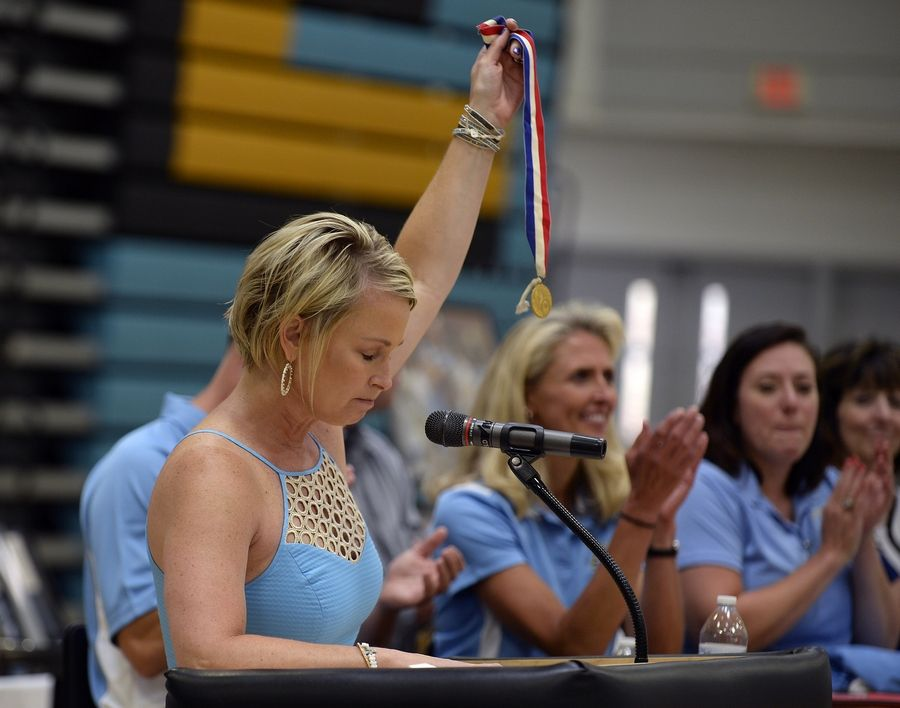 Mary Spielman, who played for legendary Maine West girls basketball coach Derril Kipp from 1985-89, holds her state championship medal up high before about 500 people who celebrated his life during a memorial service Saturday at the Des Plaines high school.