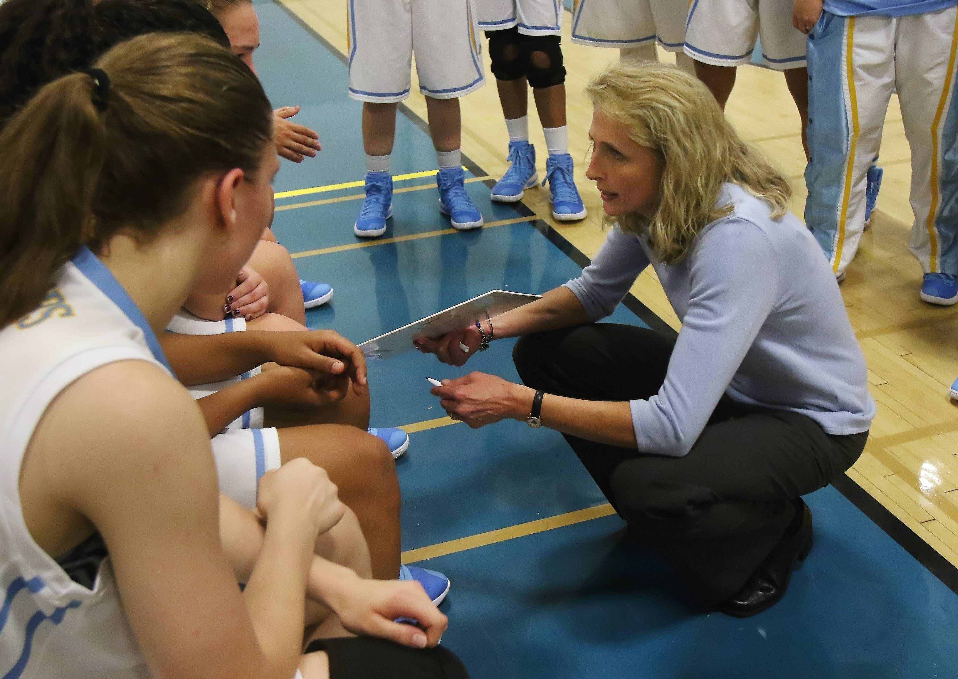 Maine West coach Kim de Marigny talks to her players during the Warriors' season-opening win against Wheeling.