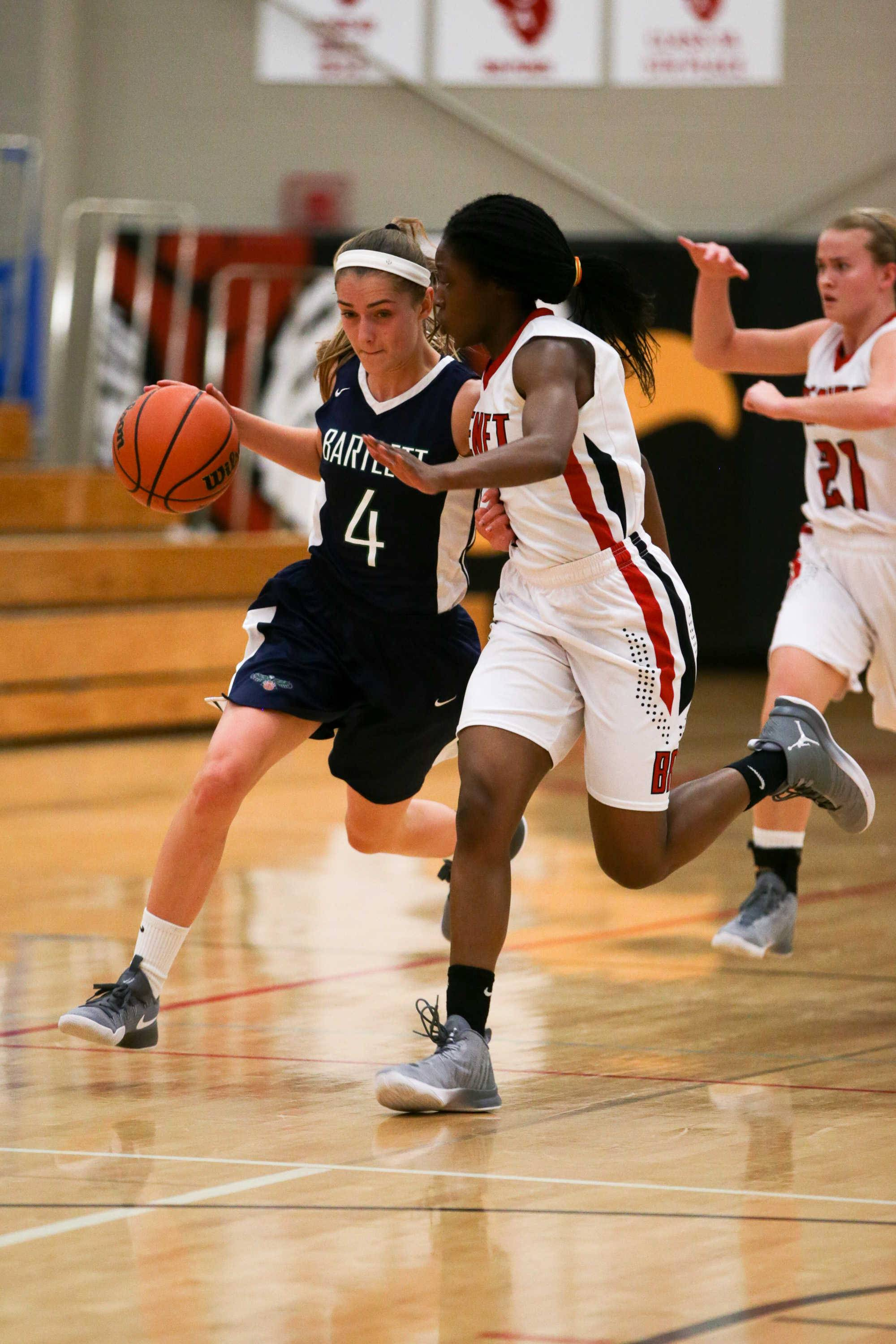 Bartlett guard Kayla Hare (4) drives to the hoop against Benet guard Tsimba Malonga (1) at Benet Academy in Lisle, IL on Friday, November 18, 2016