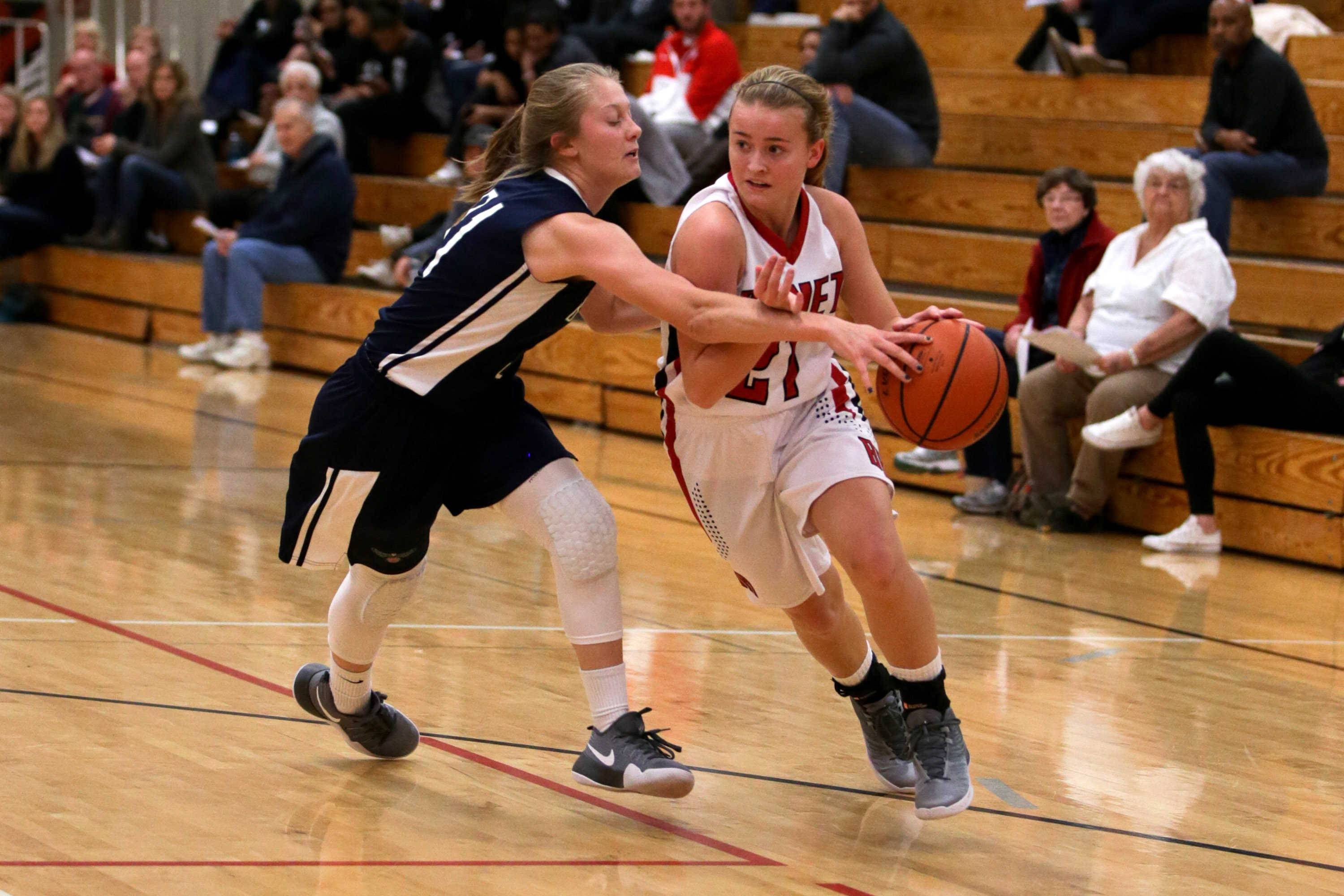 Benet guard Clara Prasse (21) drives to the hoop against Bartlett forward Brooke Bednarke (31) at Benet Academy in Lisle, IL on Friday, November 18, 2016
