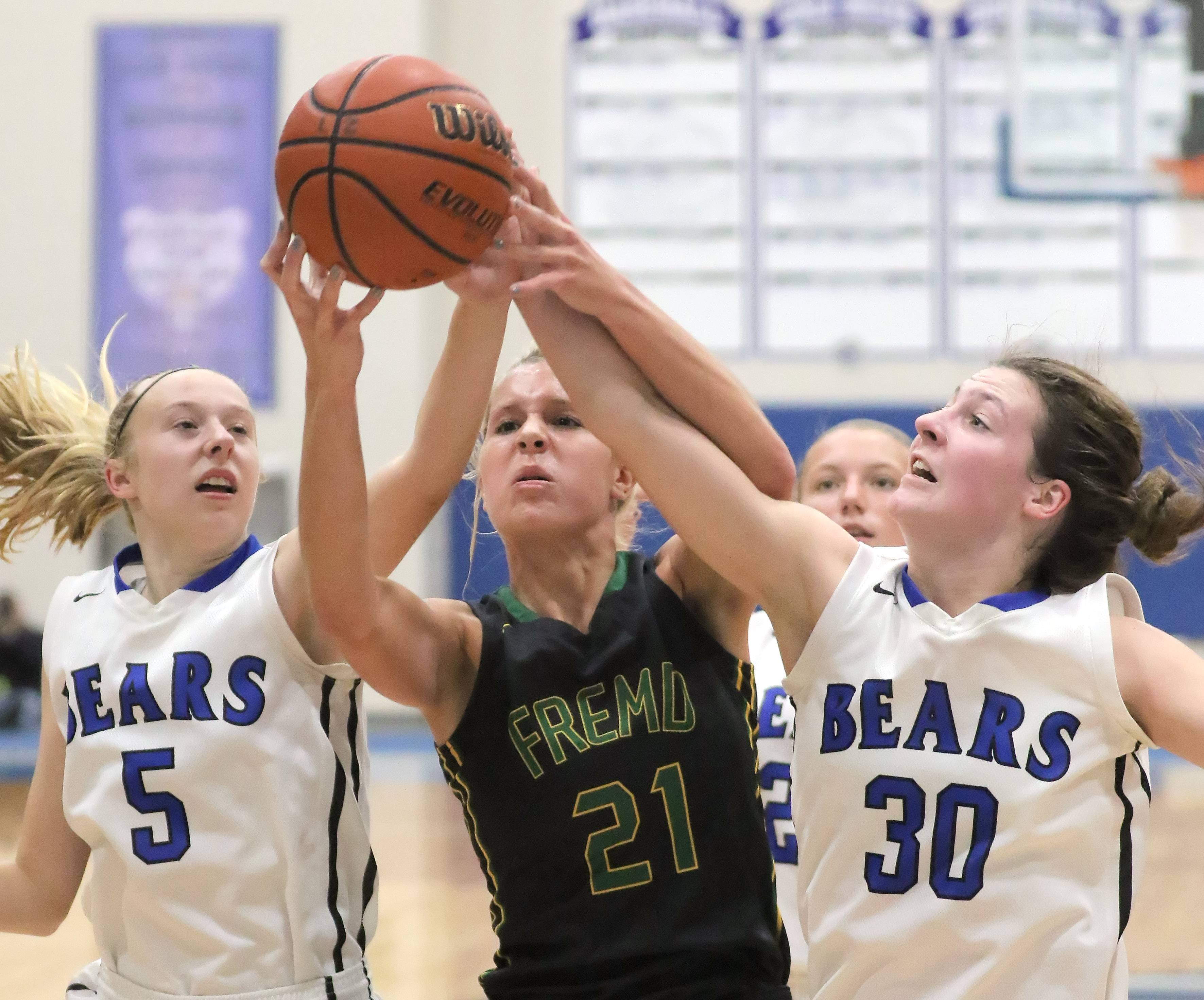 Fremd's Grace Tworek (21) battles for a rebound with Lake Zurich's Ella Gilbertson (5) and Grace Kinsey on Wednesday at Lake Zurich.
