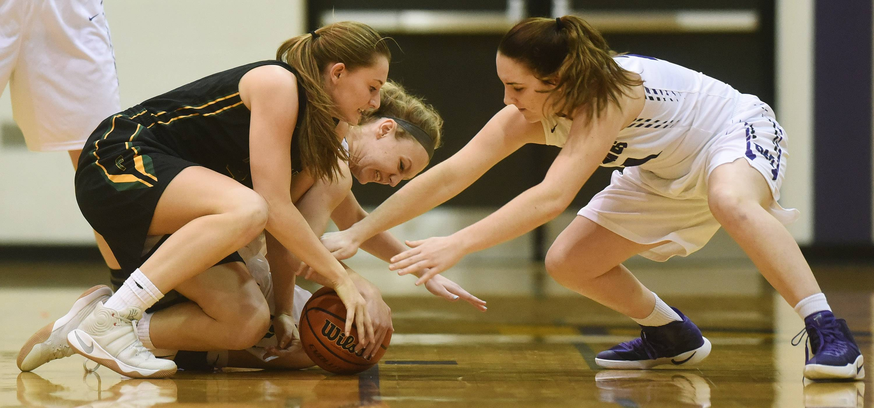 Fremd's Missy Adrian, left, goes to the floor for a loose ball with Rolling Meadows' Lily Greifenstein, middle, and Caili Hosler during Tuesday's game.