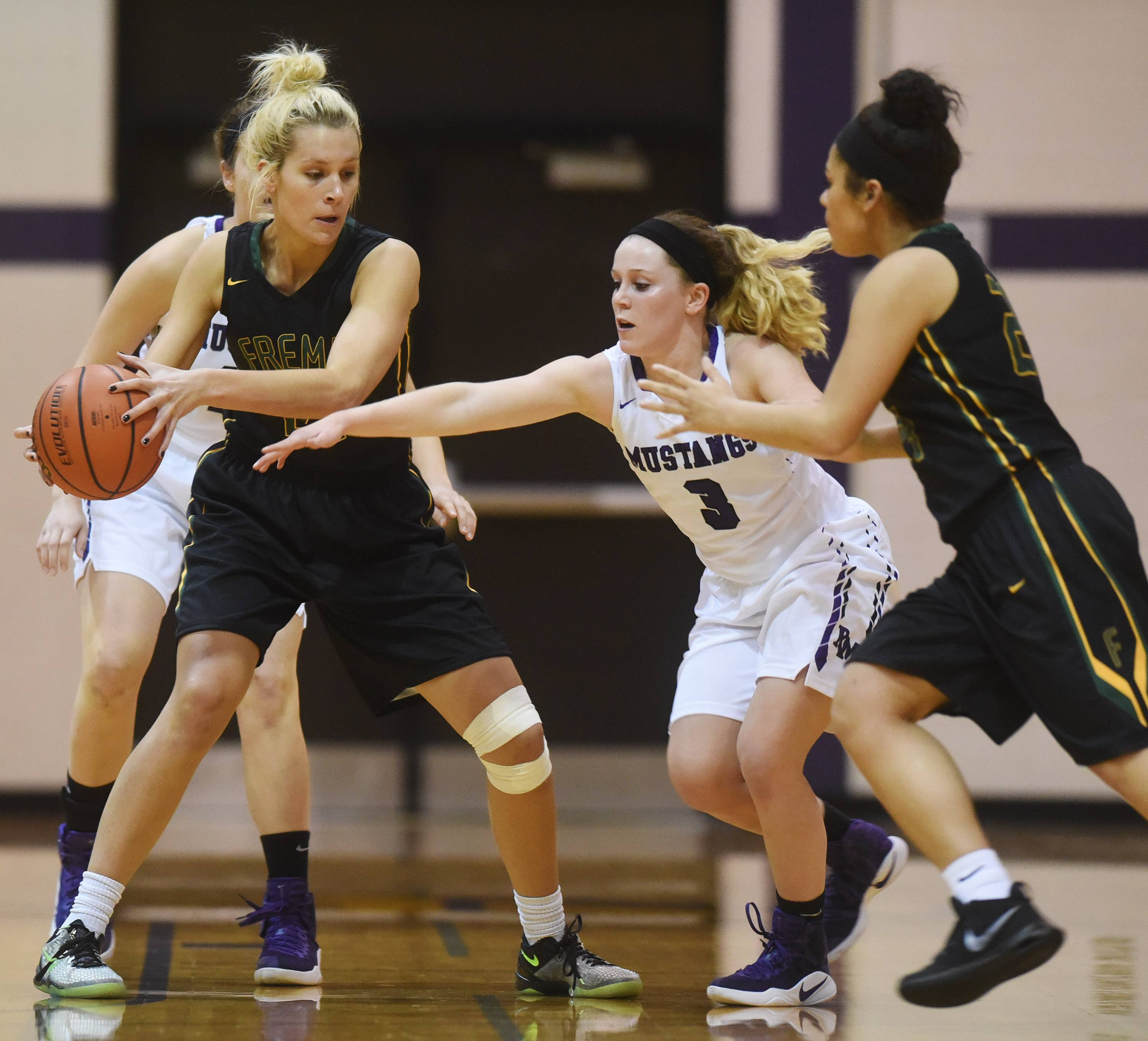 Fremd's Grace Tworek, left, looks to make a move to the basket against the Rolling Meadows defense including Clare Preissing (3) during Tuesday's game.