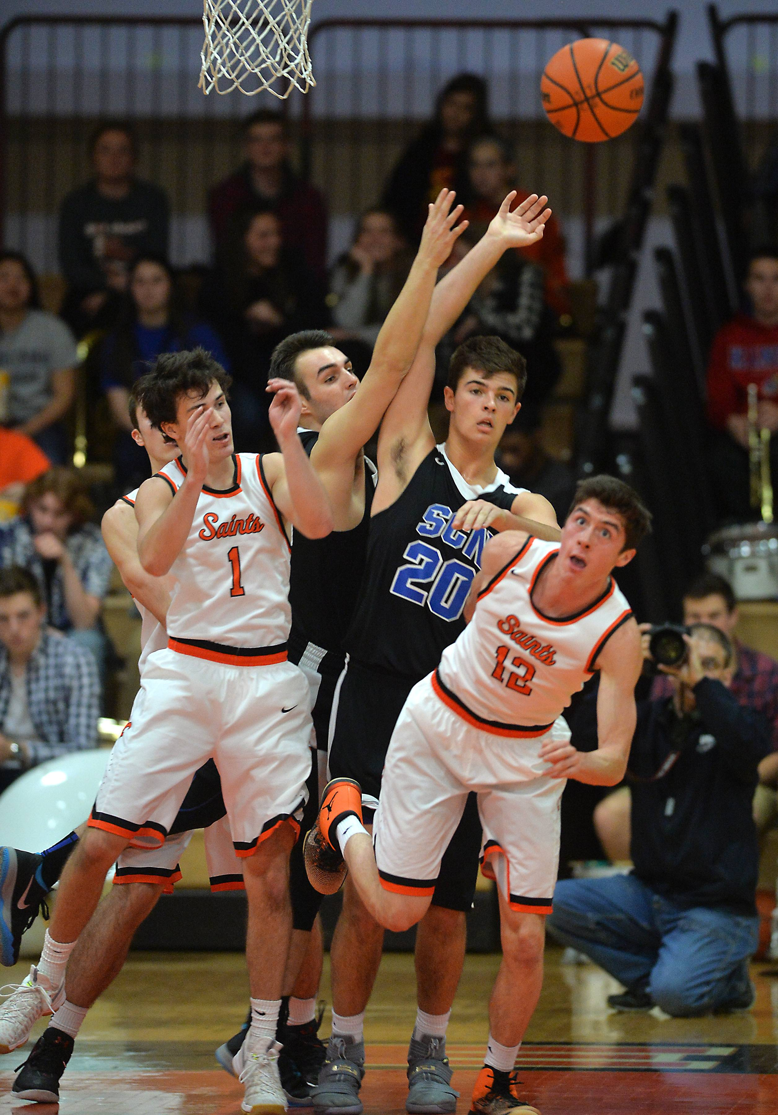 St. Charles East's Alec Champine (1) and Nate Ortiz (12) battle St. Charles North's Cade Calaghan for a rebound in the first quarter Saturday.