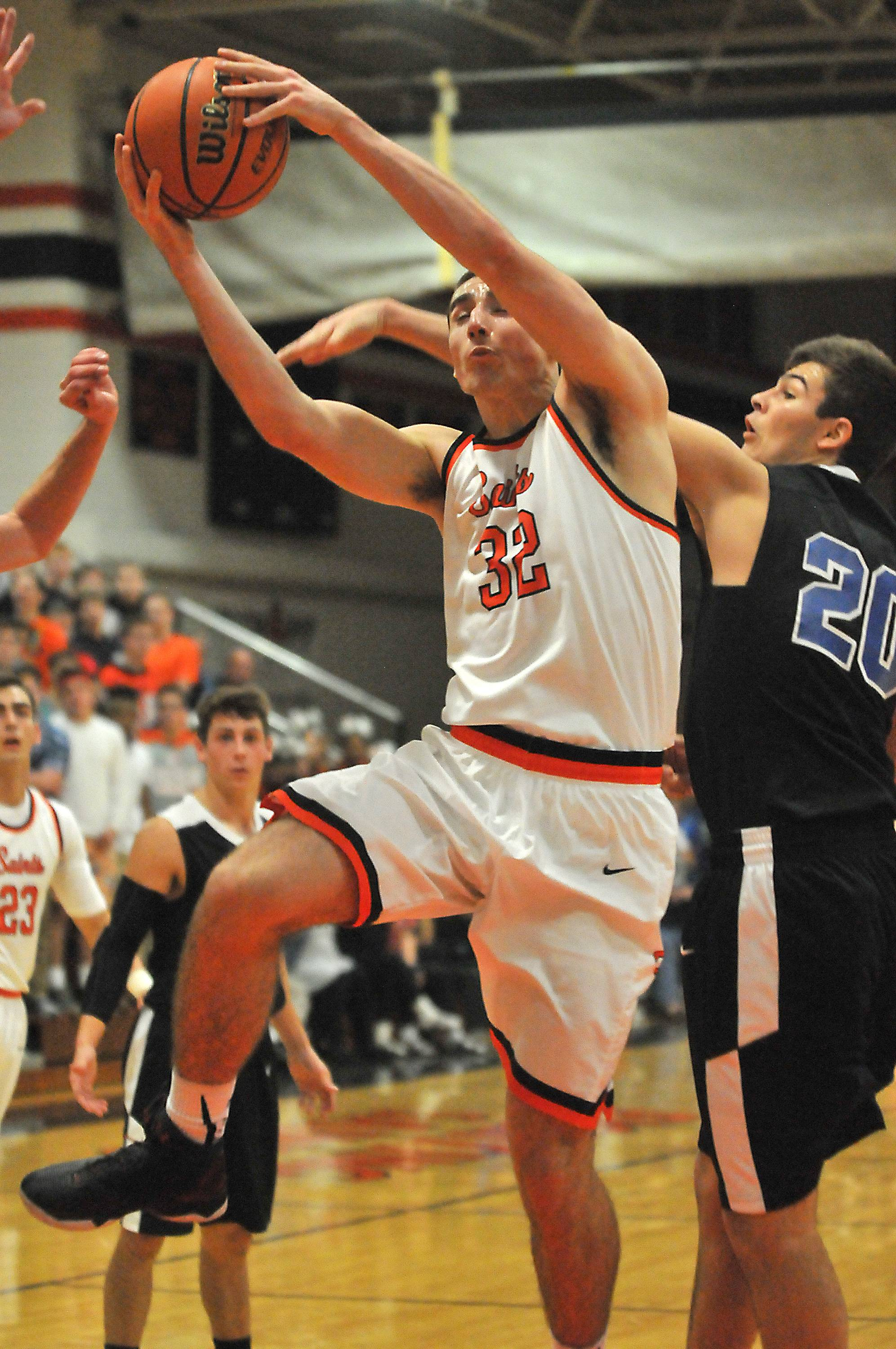 St. Charles East's Justin Hardy drives to the hoop while shadowed by St. Charles North's Kyle King in the second quarter Saturday at East.