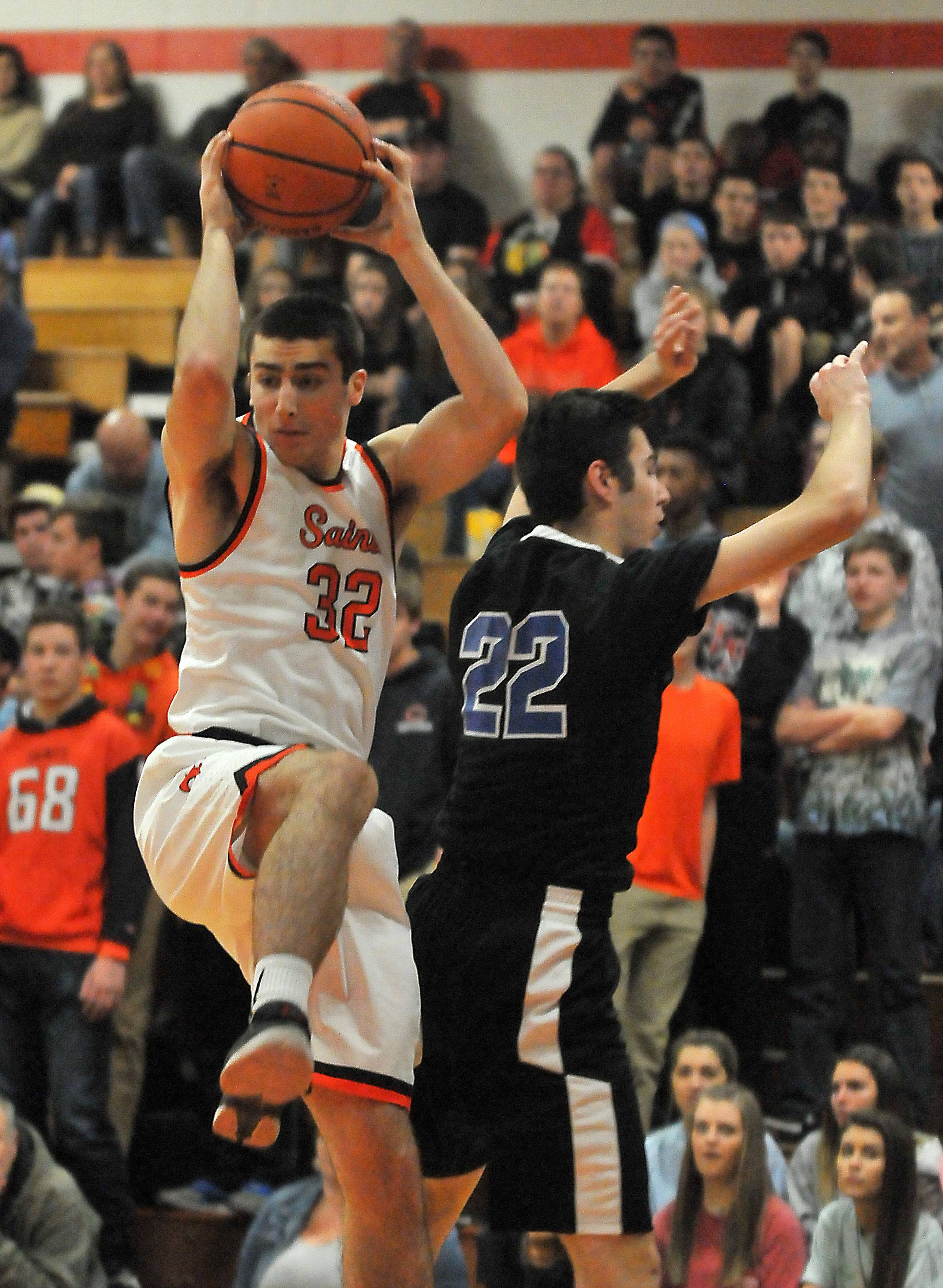 St. Charles East's Zach Mitchell beats St. Charles North's Cade Callaghan to a rebound in the first quarter Saturday at East.