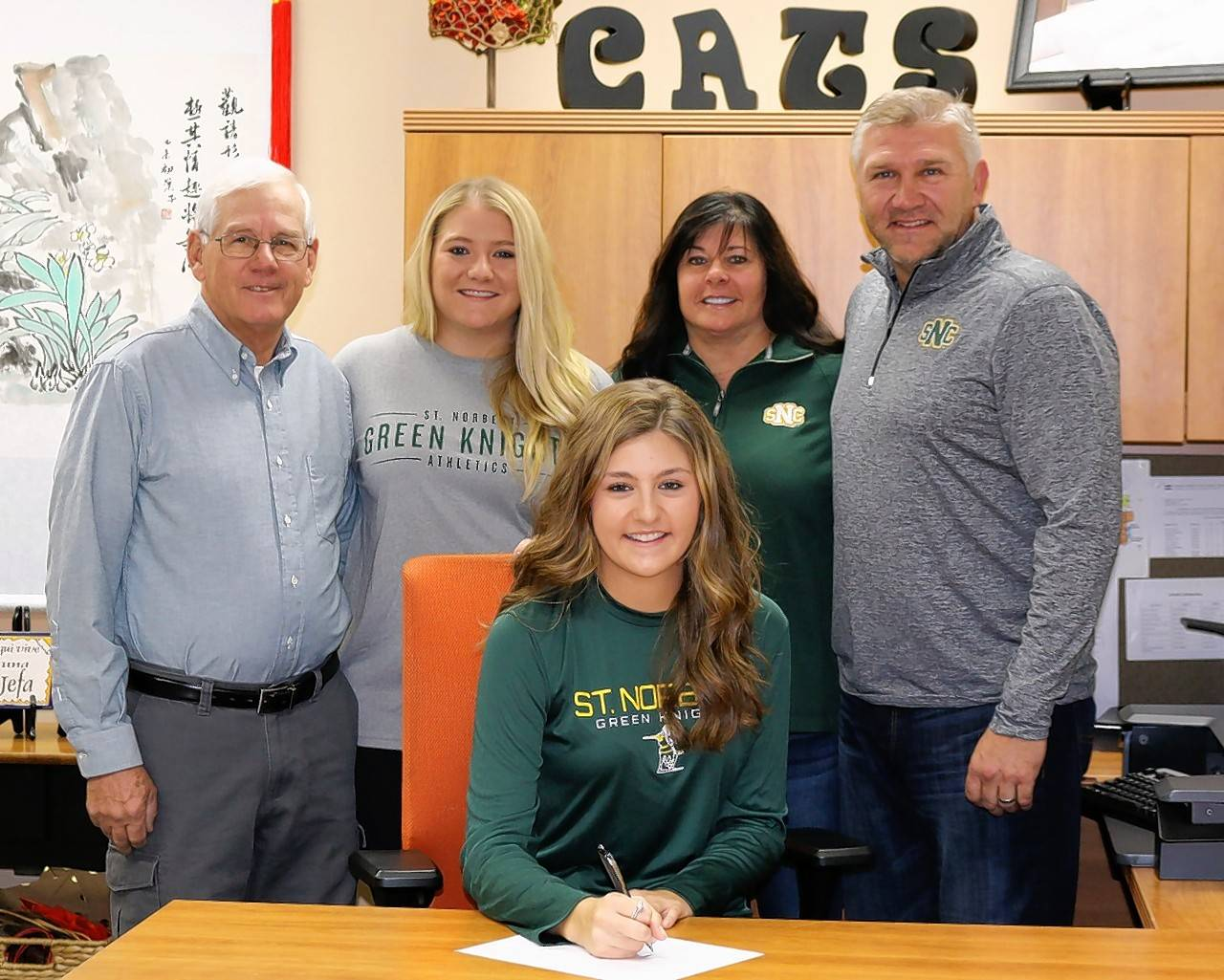 Libertyville's Lauren Paulson signs her commitment to play tennis at St. Norbert College. Pictured behind her from left are coach Craig Hunter, sister Sarah Paulson and parents Tammy and Stephen Paulson.