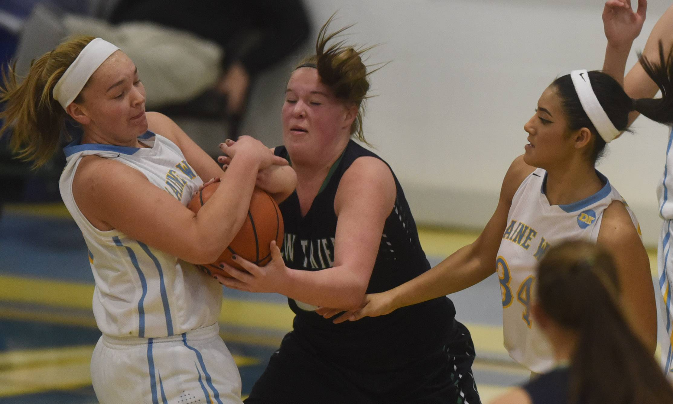 Maine West's Allison Pearson, left, takes the ball from New Trier's Jacqueline Vinson during Tuesday's game in Des Plaines.