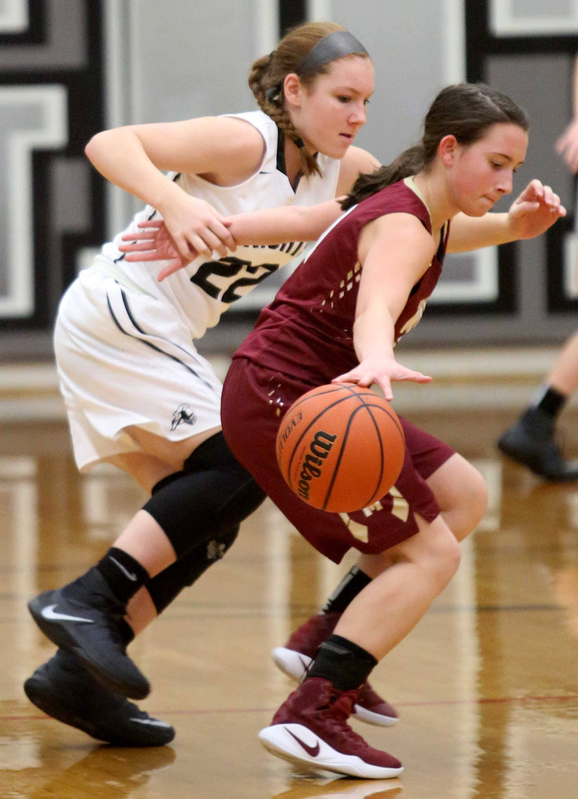 Kaneland's Maddy Wheatley, left, keeps up with Morris' Paige Valentine during varsity basketball action at Kaneland Tuesday night.