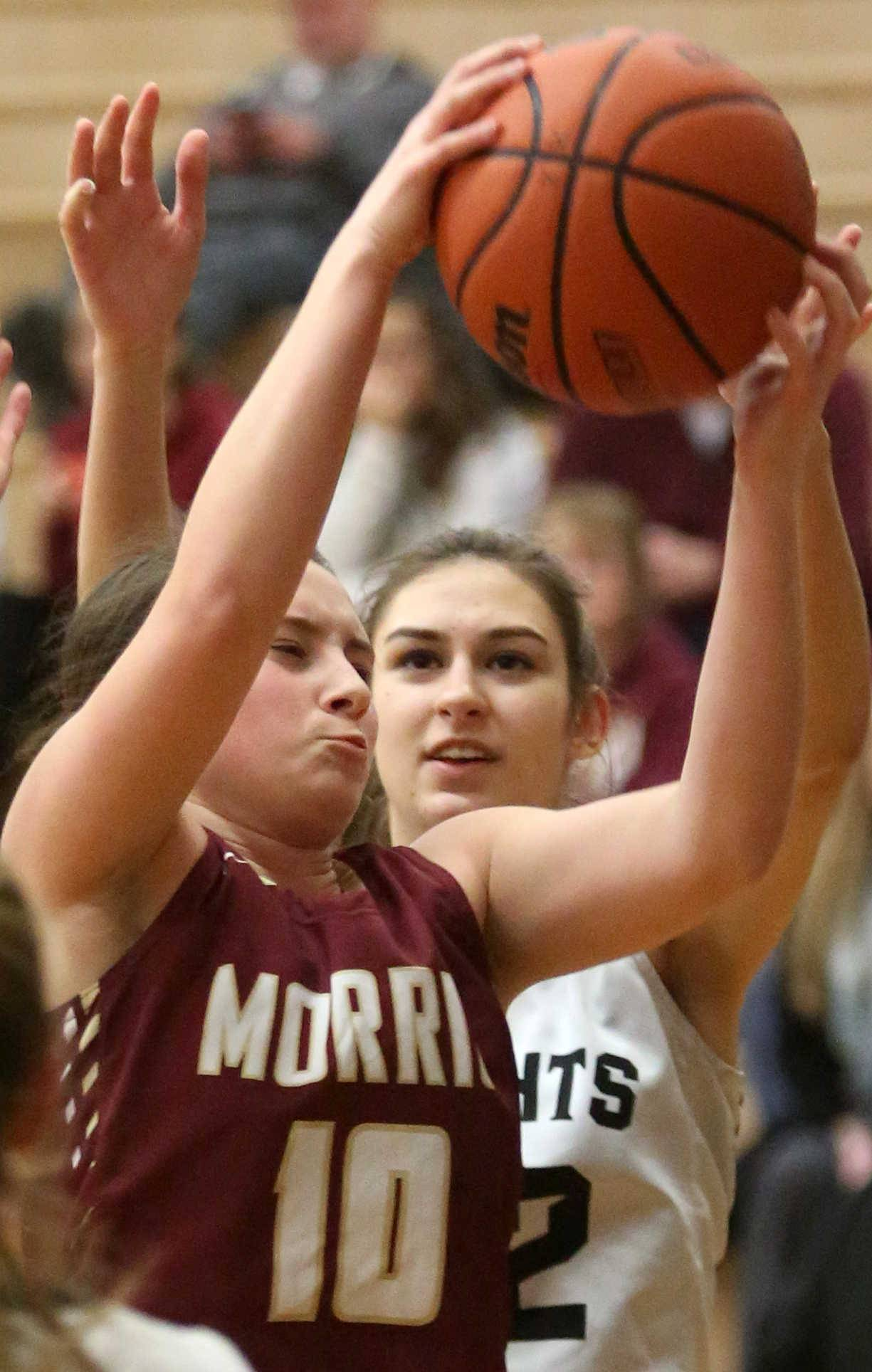 Morris' Paige Valentine snags a rebound in front of Kaneland's Grace Ringel during varsity basketball action at Kaneland Tuesday night.