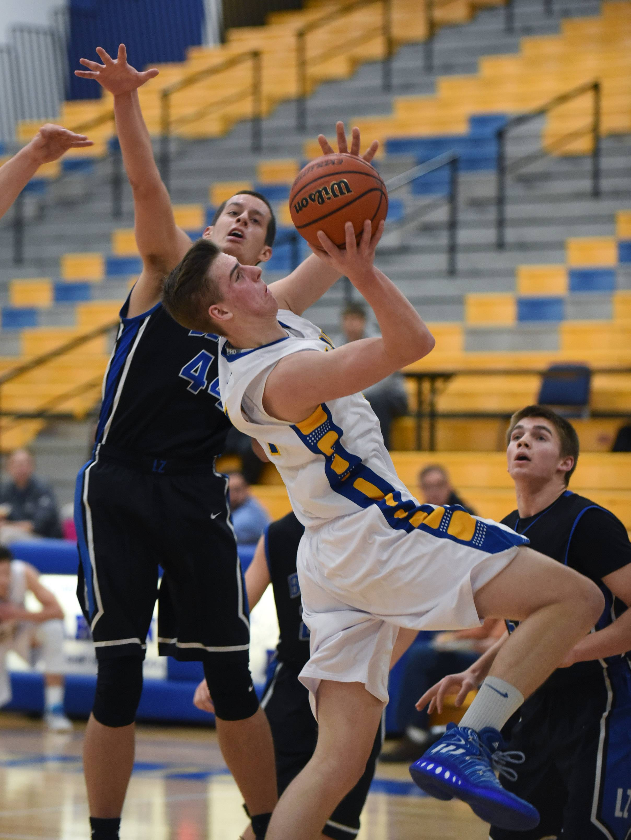 Warren's Declan O'Connor takes a shot under pressure from Lake Zurich's Chris Trybula (44) during Thursday's boys basketball game in Gurnee.