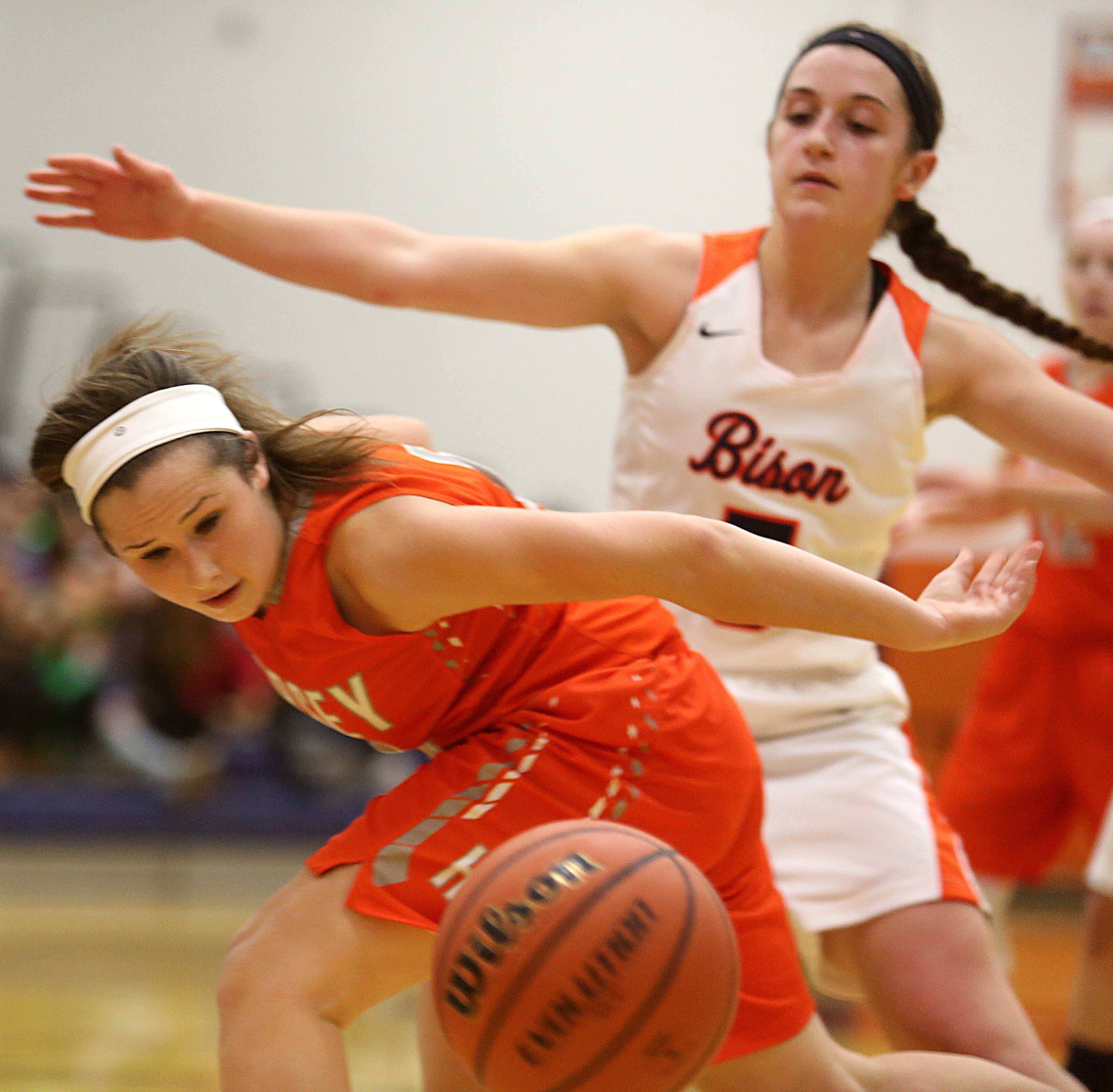 Hersey's Kelly Weyhrich, foreground, swats the ball away as Buffalo Grove's Jackie Bickhaus keeps her eyes on the action at Buffalo Grove on Friday night.