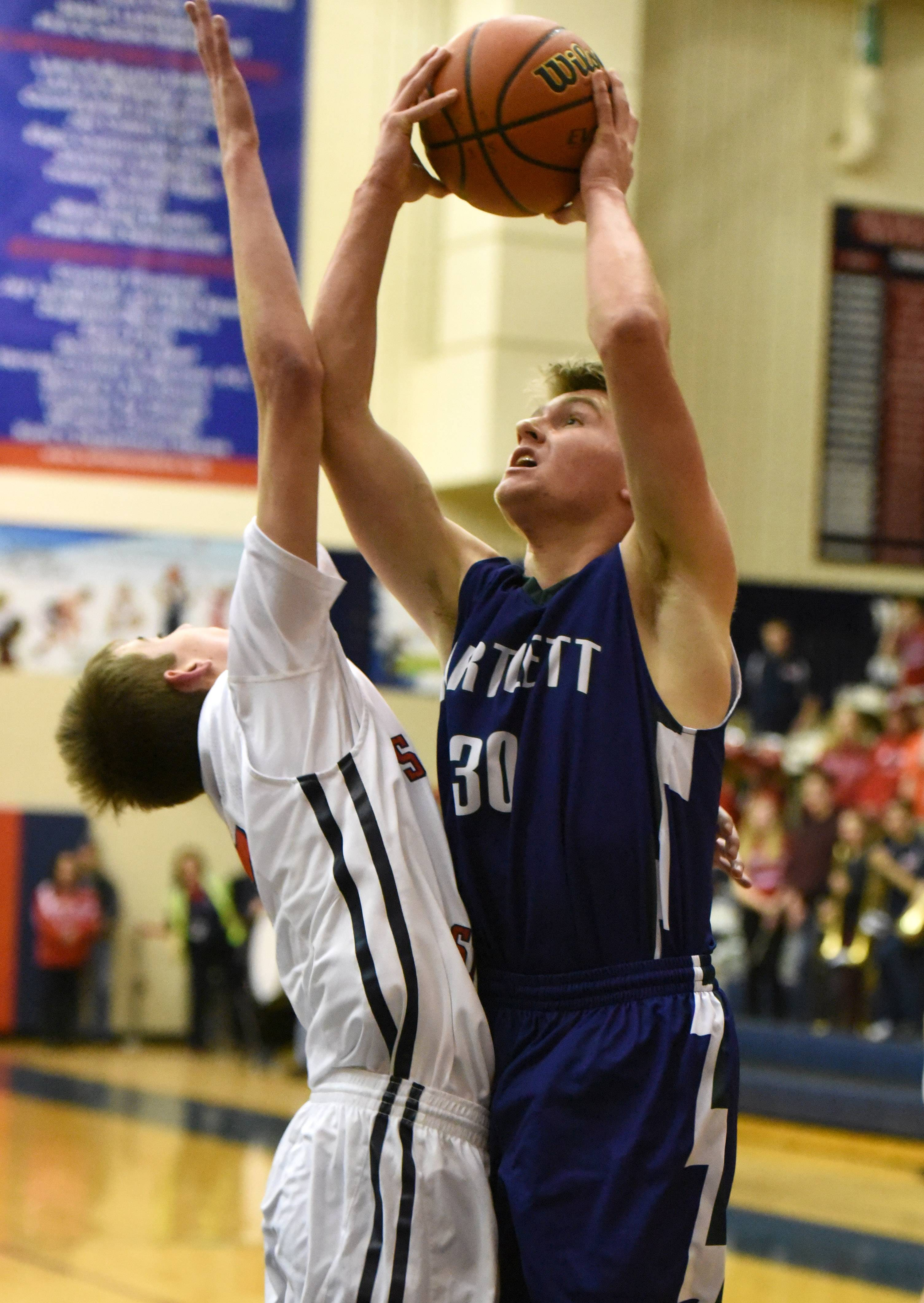 Bartlett's Ben Fisher puts up a shot with South Elgin's Christopher Hankins defending during Friday's game in South Elgin.