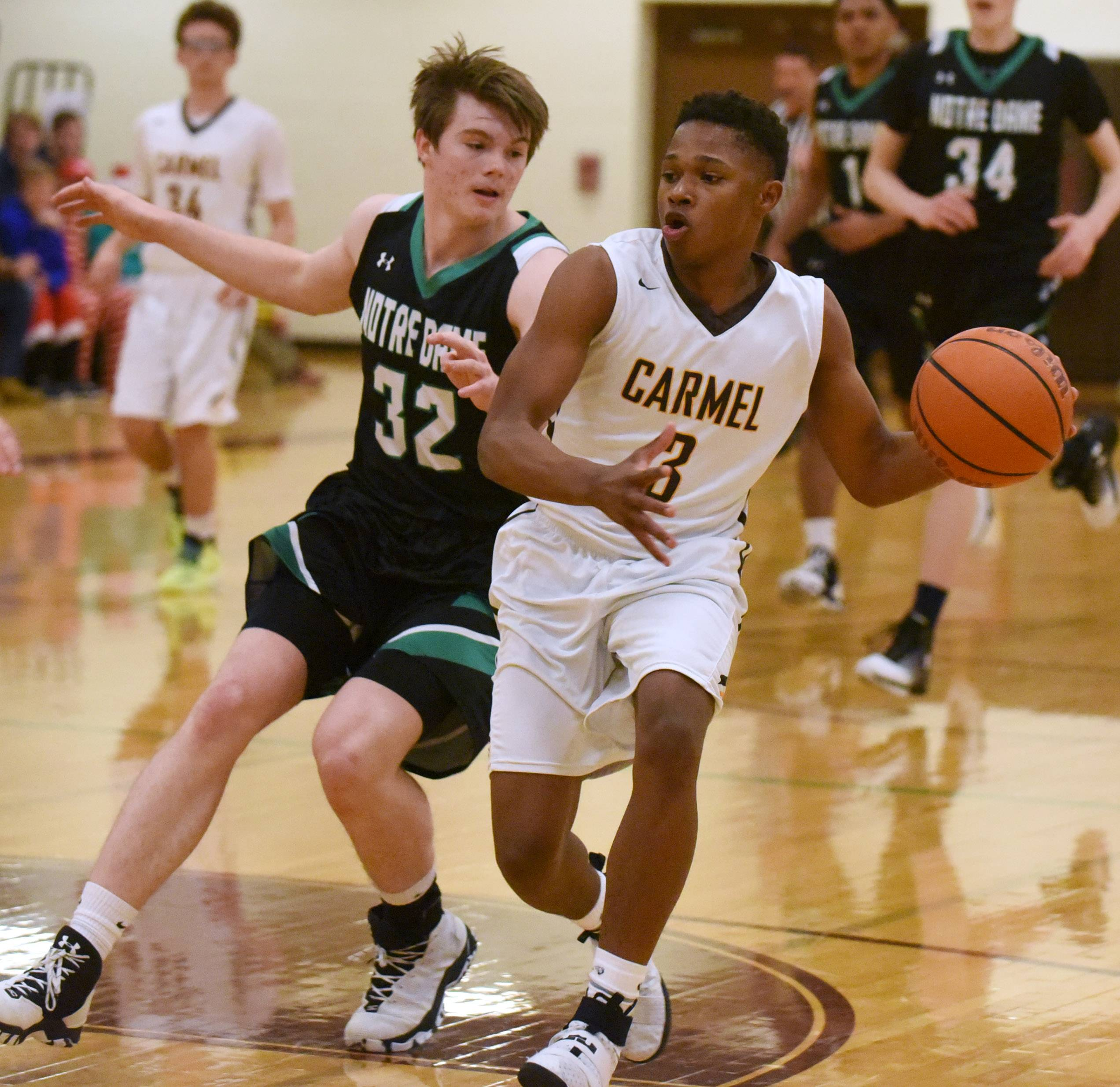 Carmel's Zion Kilpatrick (3) heads to the basket past Notre Dame's Chris Heinichen on Friday in Mundelein.