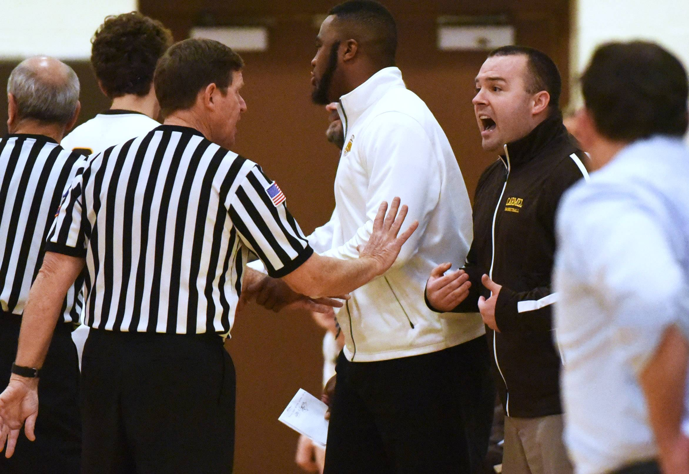 Carmel's boys head varsity basketball coach Zack Ryan, right, exchanges words with the refs during Friday's game against Notre Dame in Mundelein.