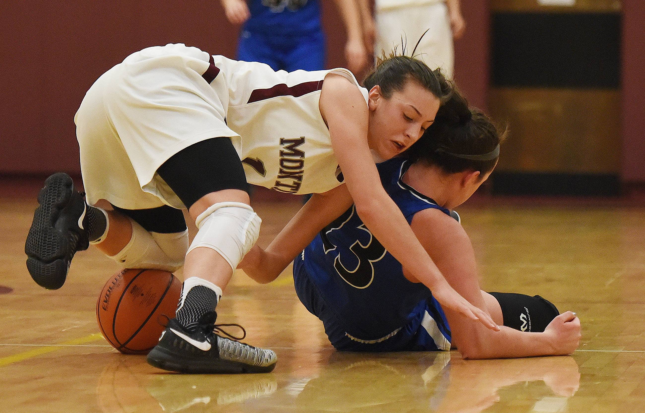 Montini's Claudia Kunzer (01) and Geneva's Margaret Whitley (23) scramble for a ball during the Montini vs. Geneva at Montini girls basketball tournament semifinals Thursday.