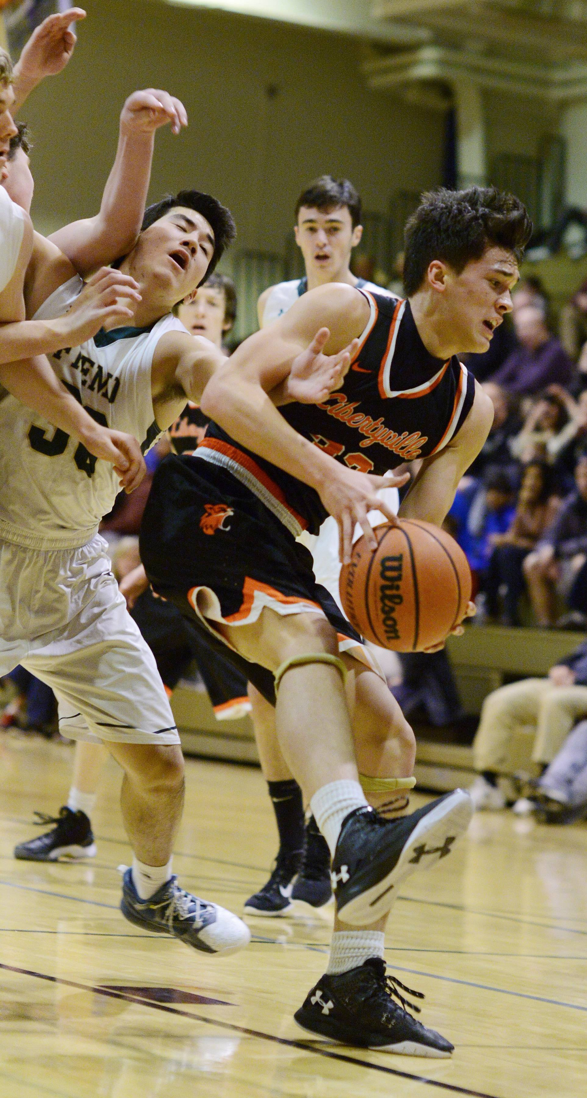 Libertyville's Harrison Bach, right, draws contact from Fremd's Ryan Martin during semifinal play in the Wheeling Hardwood Classic on Thursday.
