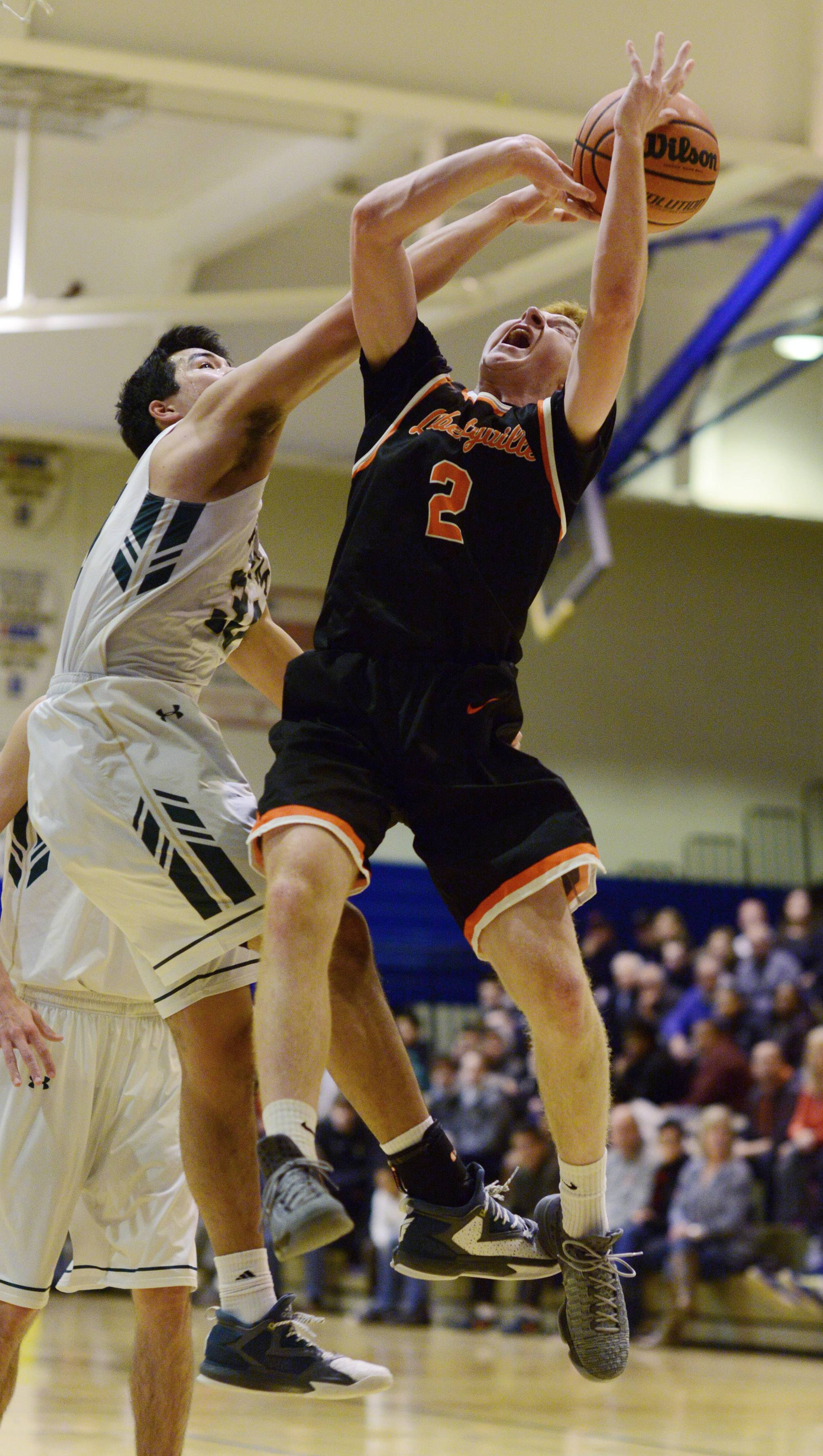 Libertyville's Ryan Wittenbrink, right, tries to get past Fremd's Ryan Martin at the basket during semifinal play in the Wheeling Hardwood Classic on Thursday.