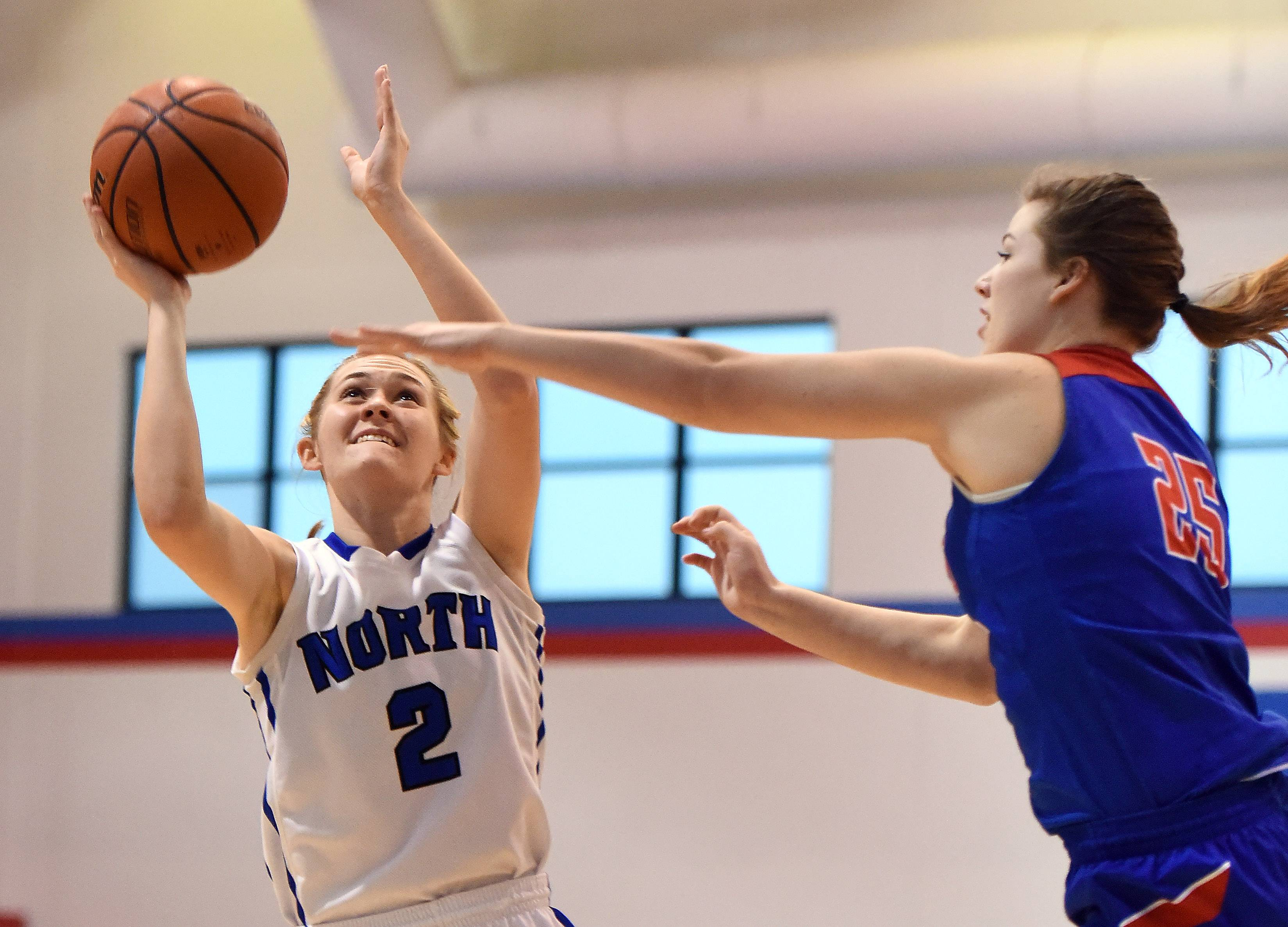 St. Charles North's Anna Davern puts up a shot with Dundee-Crown's Allison Michalski defending during the consolation finals at the 34th annual Charger Classic basketball tournament in Carpentersville Thursday.