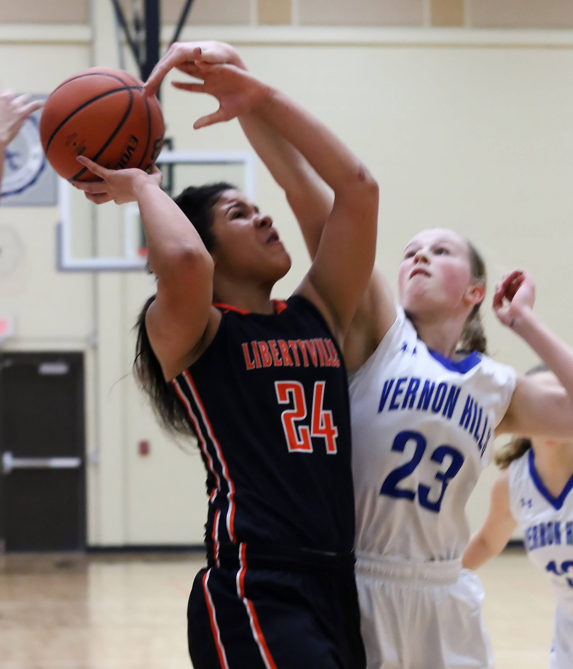 Libertyville guard Zi Tompkins has her shot blocked by Vernon Hills forward Becky Bahlmann during tournament play Thursday at Libertyville.