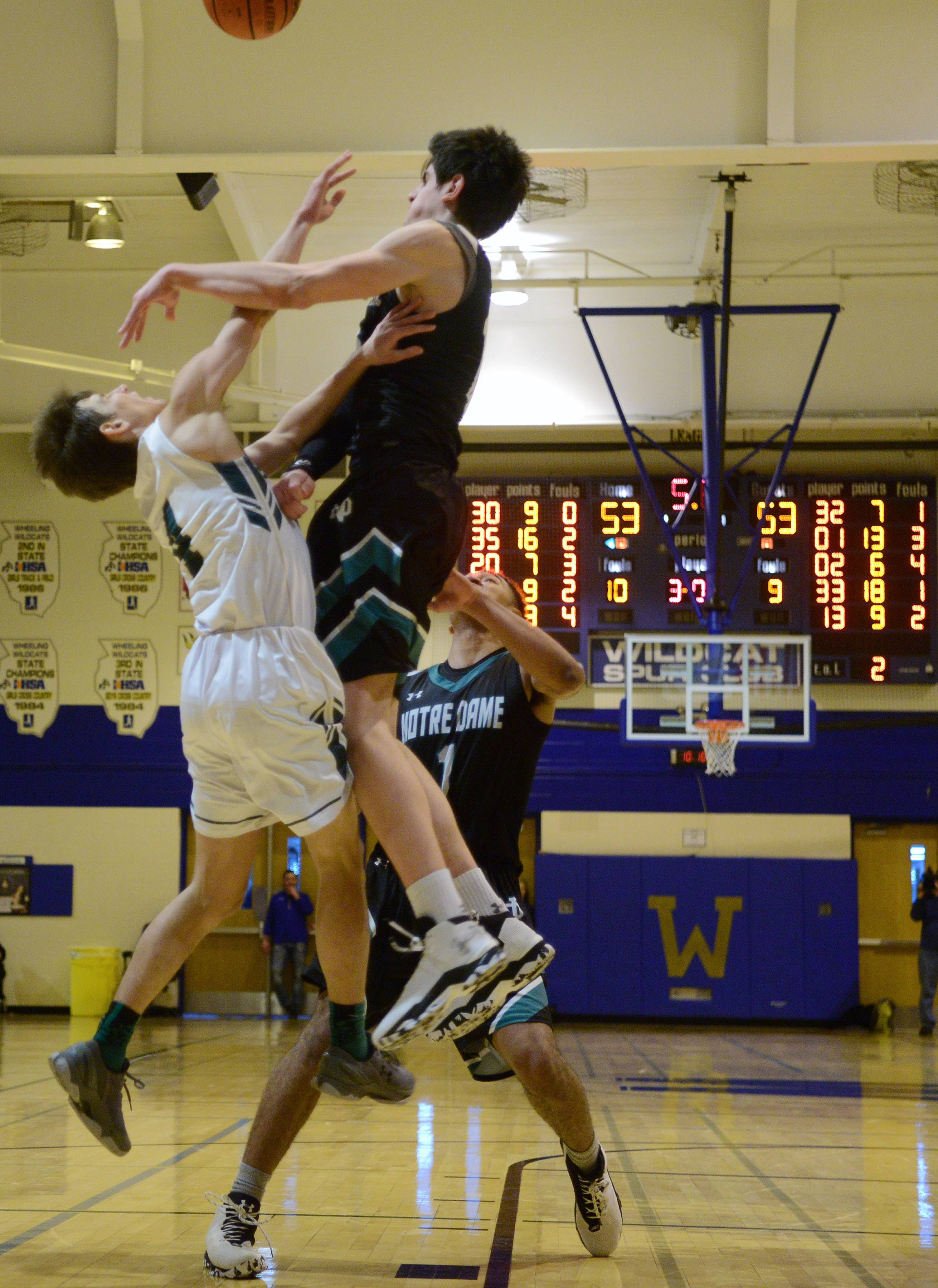 With the game tied at 53-53 in overtime, Fremd's Kyle Sliwa, left, collides with Notre Dame's Dusan Mahorcic during the championship game of the Wheeling Hardwood Classic on Friday.