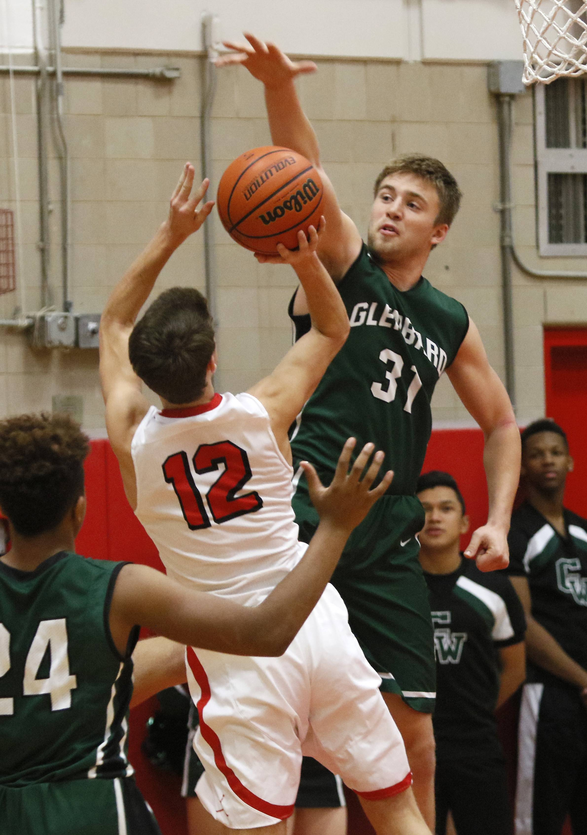 Glenbard West's Alex Pihlstrom blocks Hinsdale Central's Chris Eck's shot during boys basketball action in Hinsdale.