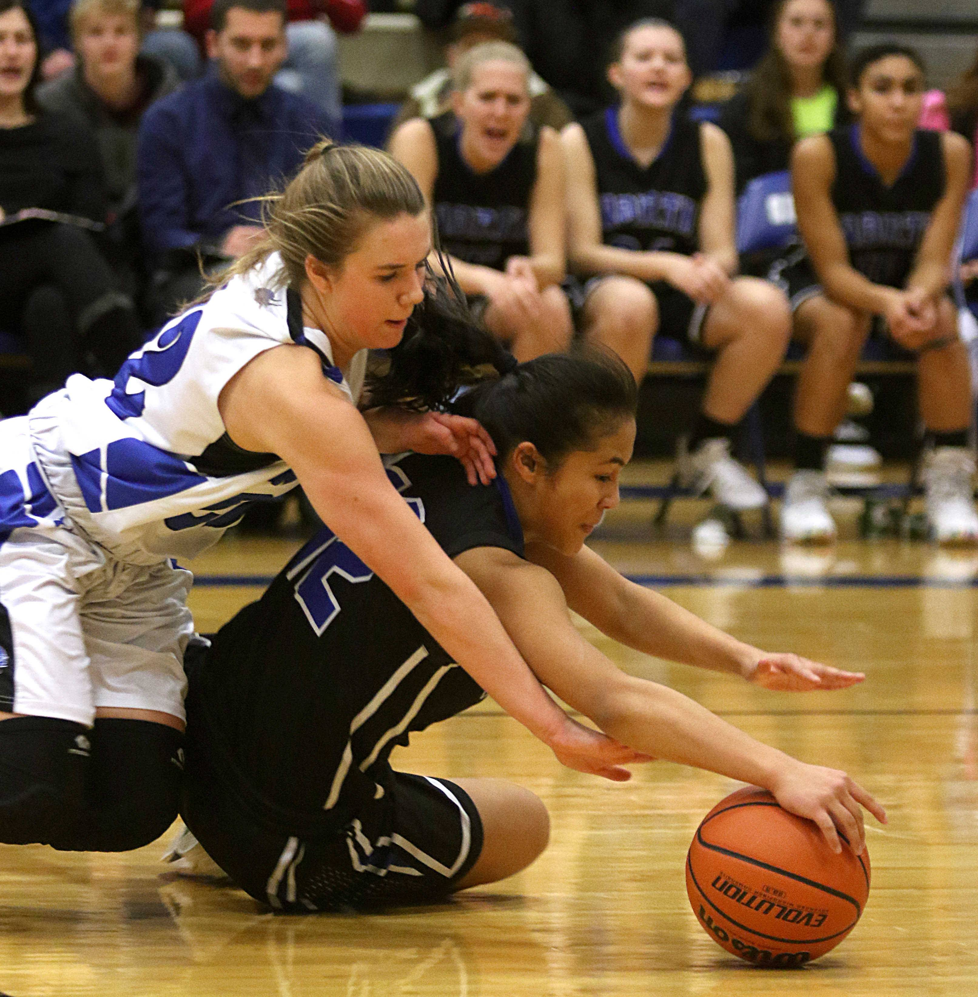St. Charles North's Leilauni Chanthaboury, bottom, and Geneva's Brie Borkowicz race for the ball during varsity girls basketball at Geneva Friday night.