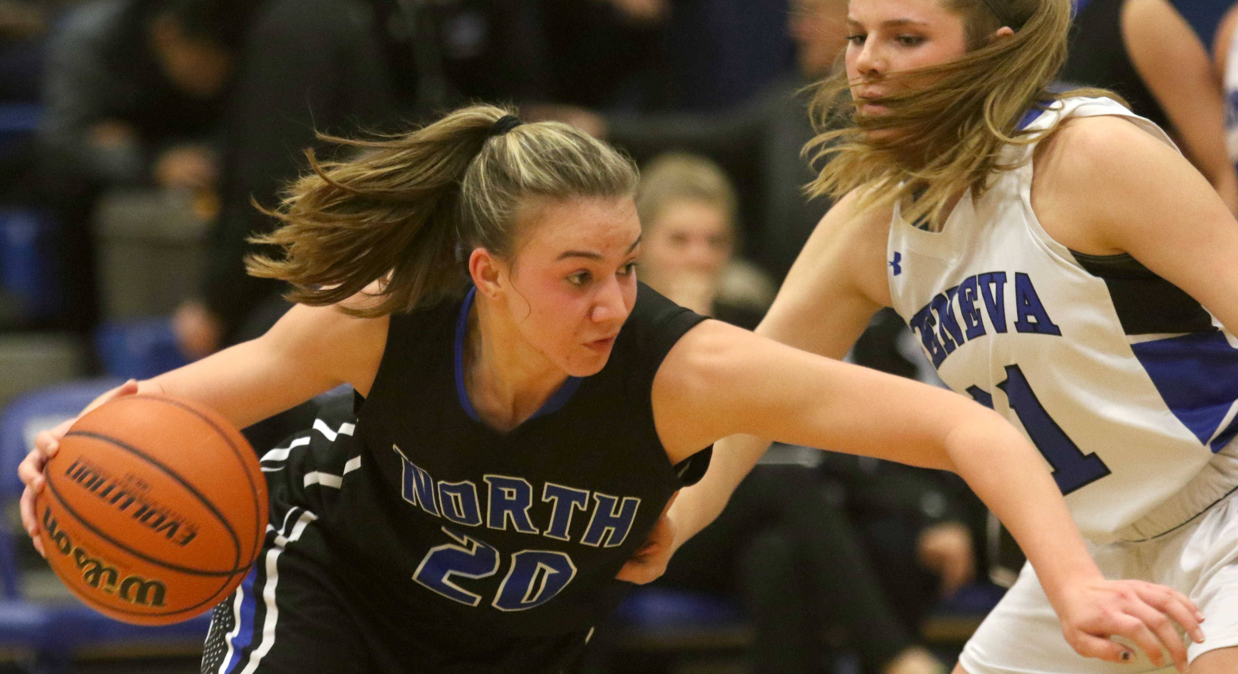 St. Charles North's Elizabeth Olsem tries to find a way past Geneva's Maddy Yelle during varsity girls basketball at Geneva Friday night.