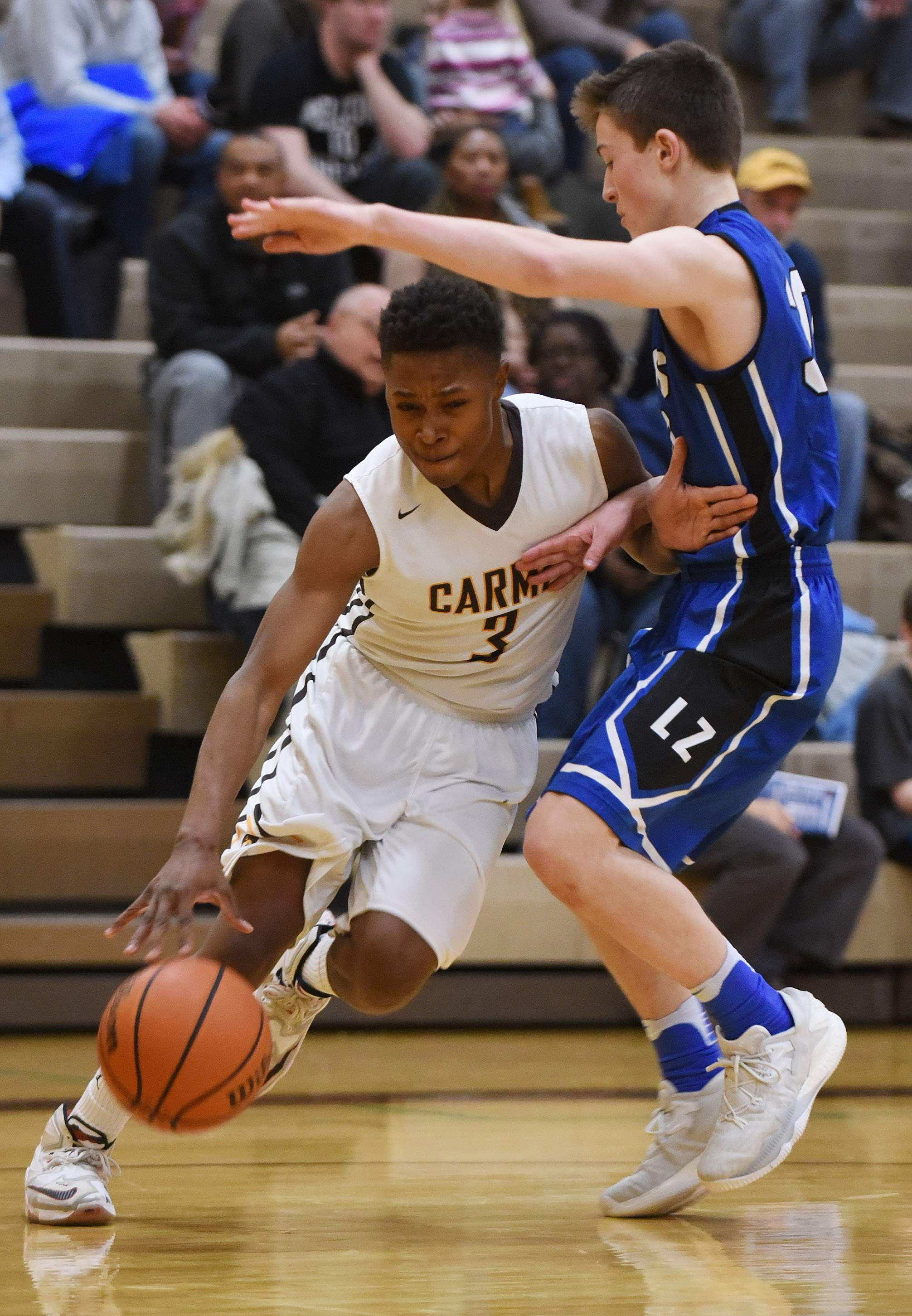Carmel's Zion Kilpatrick, left, tries to make a move past Lake Zurich's Will Tucker during Saturday's game in Mundelein.