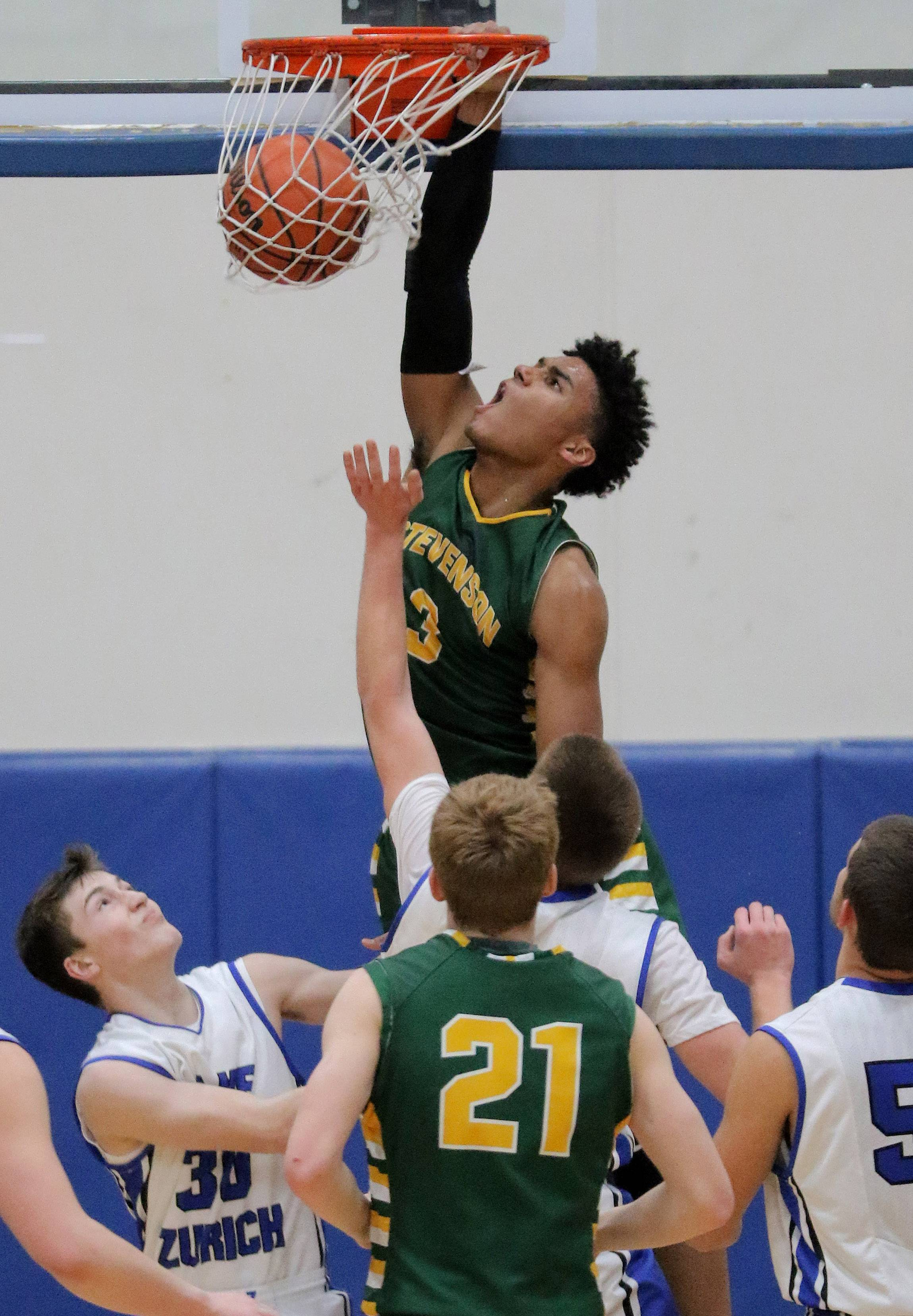 Stevenson's Justin Smith rises above a crowd for a dunk Tuesday night at Lake Zurich.