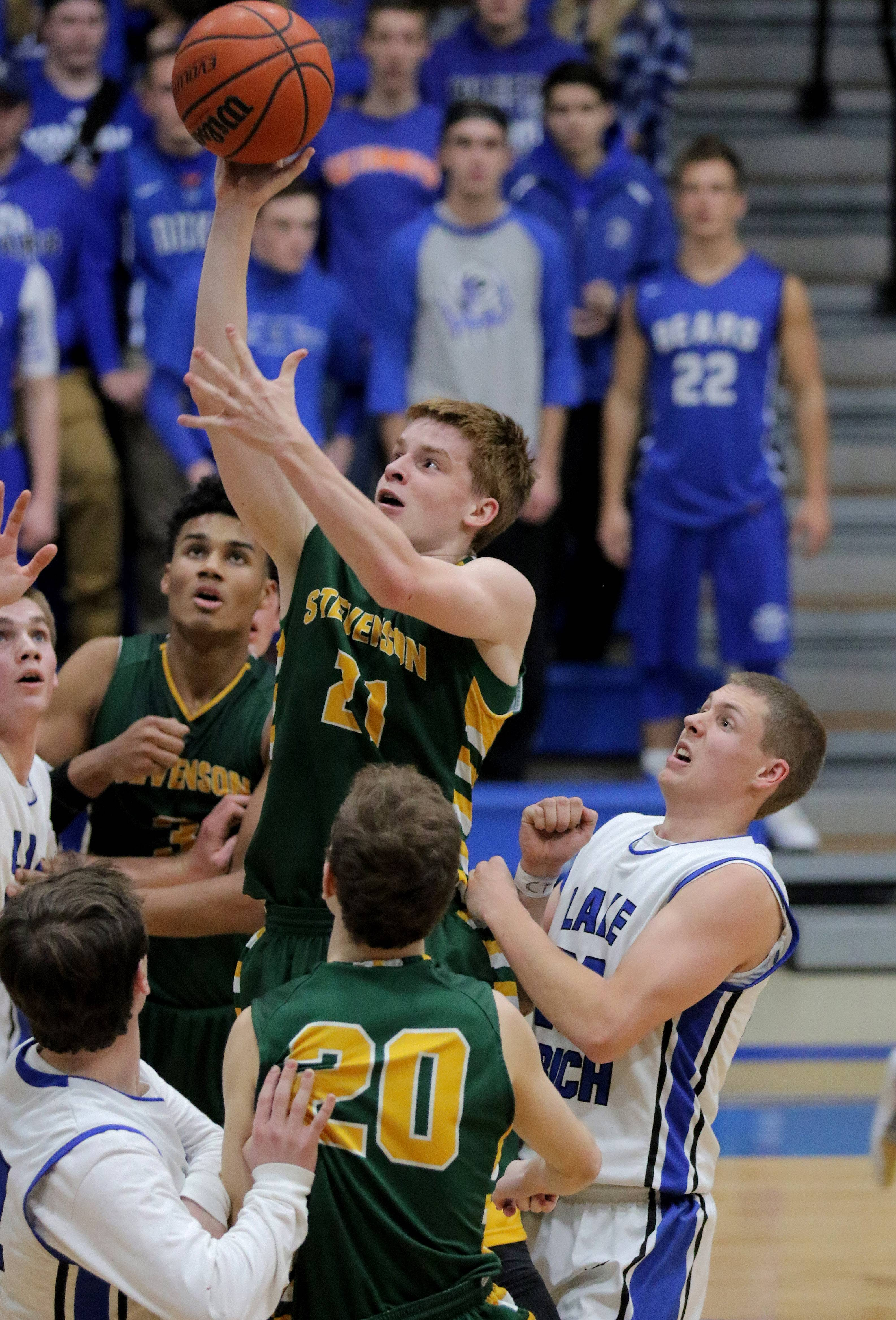 Stevenson's Jackson Qualley (21) drives to the hoop through a crowd Tuesday night in Lake Zurich.
