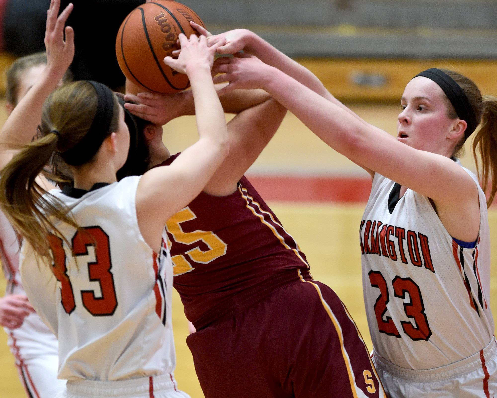 Barrington's Claire Collier (33) and Rachel Mori (23) wrestle with Schaumburg's Abigail Paolicchi for a rebound on Friday at Barrington.