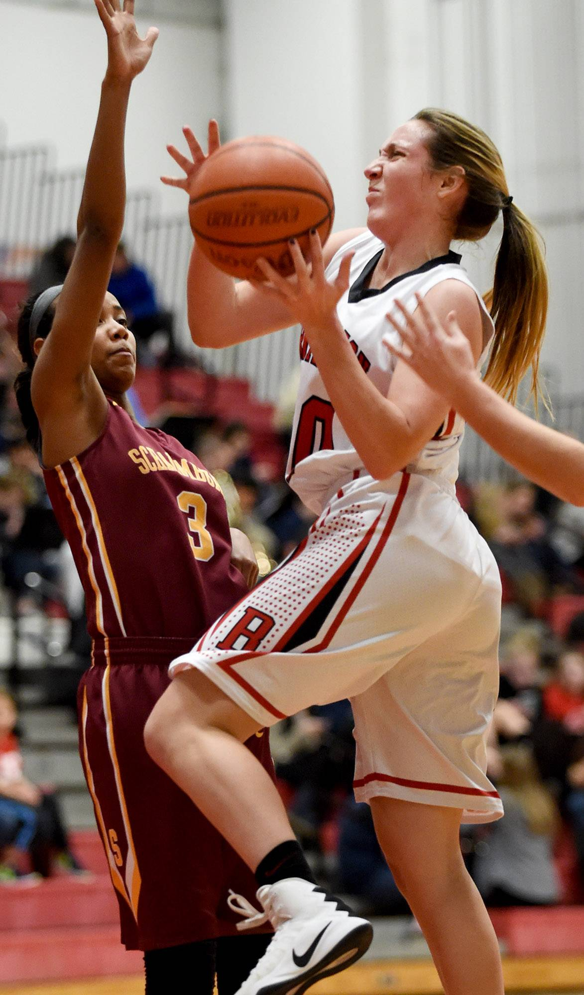 Schaumburg's Kayla Patterson (3) tries to defend as Barrington's Tori Meyer (20) on a driving layup Friday at Barrington.