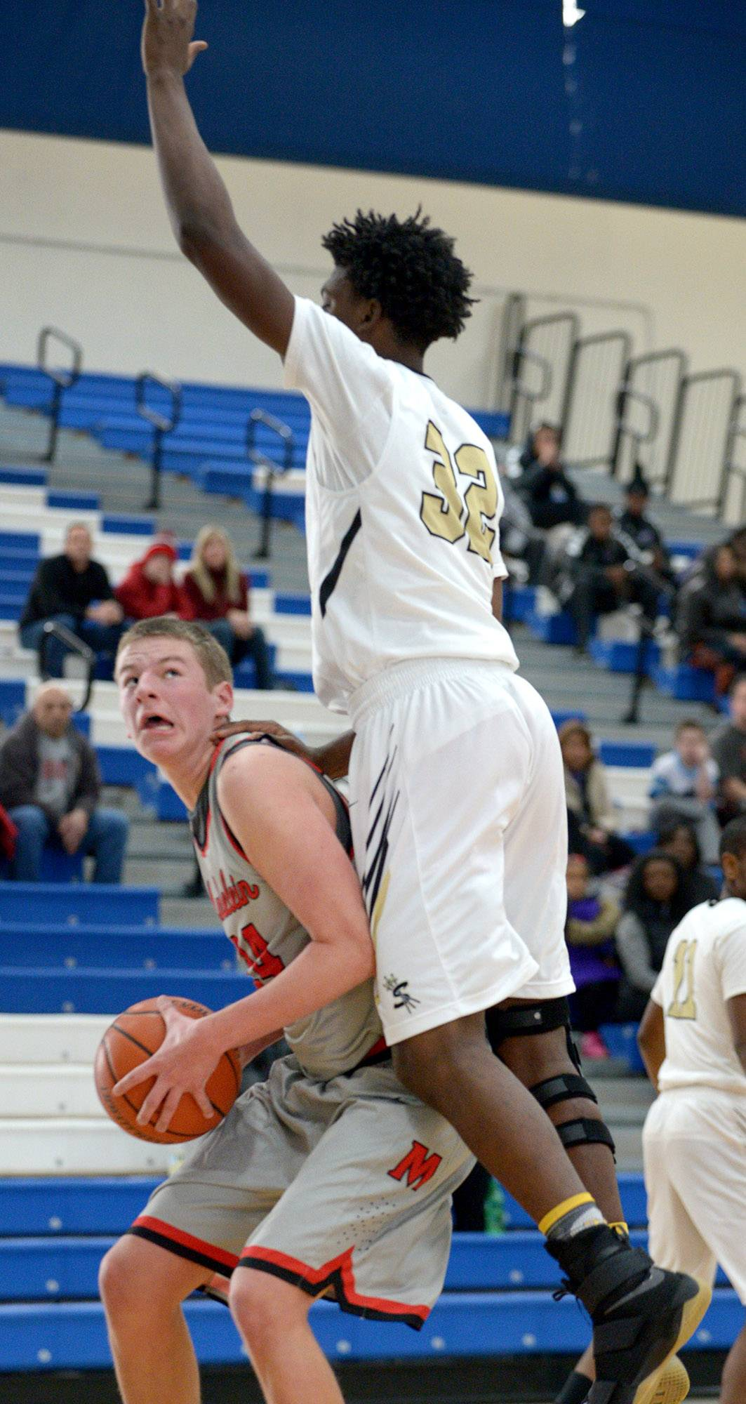 Streamwood's Keenan Cole (32) leaps to block a shot from Mundelein's Jeff Bikus, who fakes him out and moves to the hoop on Saturday at Lake Zurich.