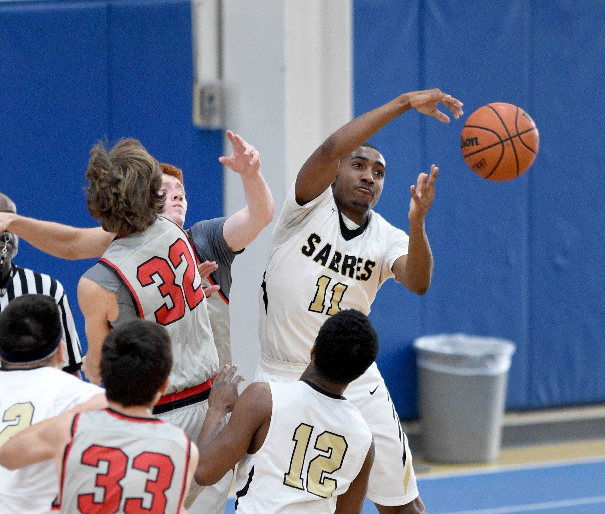 Streamwood's Keenan Evans (11) clears a lose ball under the Mundelein bucket on Saturday at Lake Zurich.