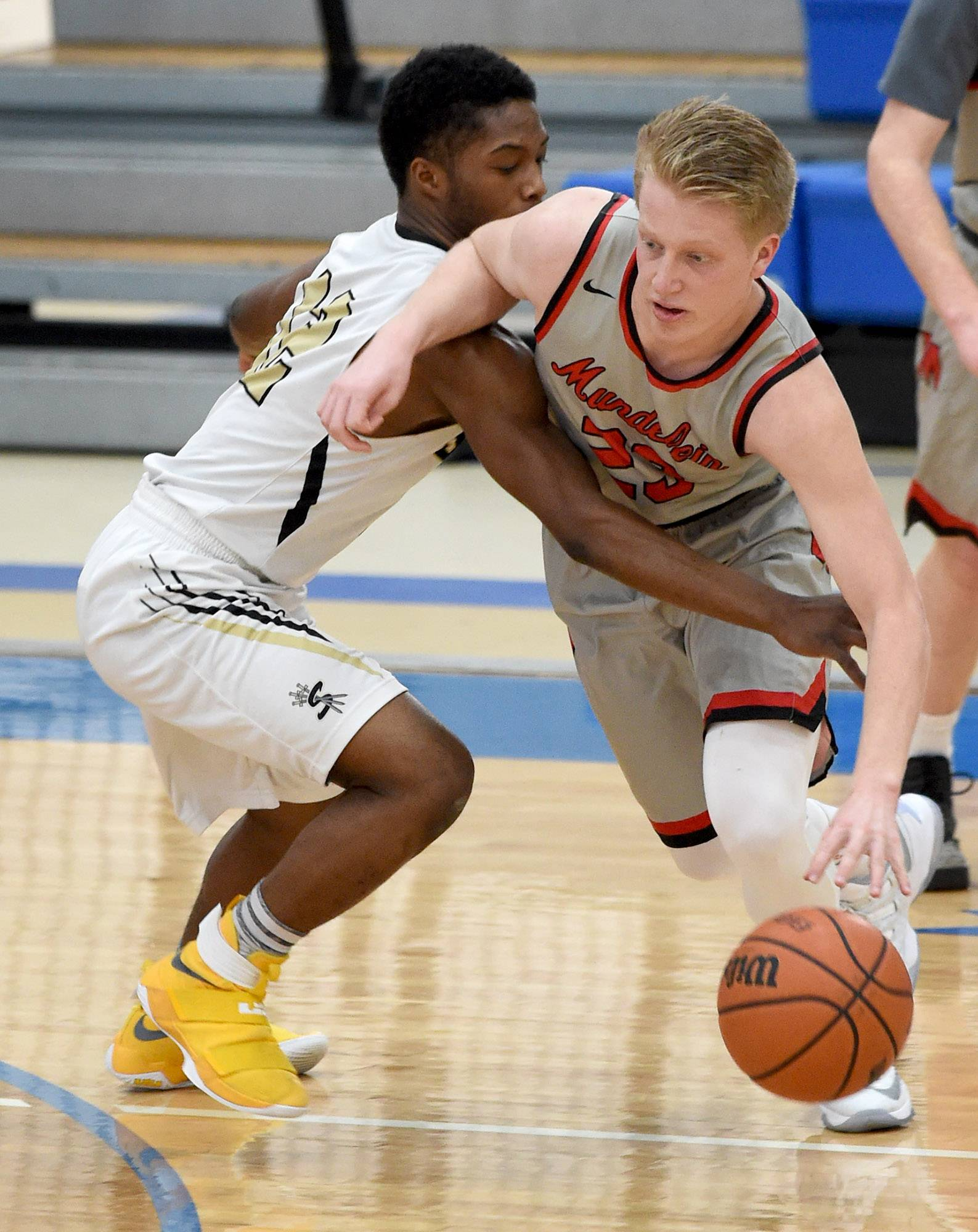 Streamwood's Antuan Patterson (12) reaches in to tip the ball from Mundelein's Tommy Marcotte (23) on Saturday at Lake Zurich.