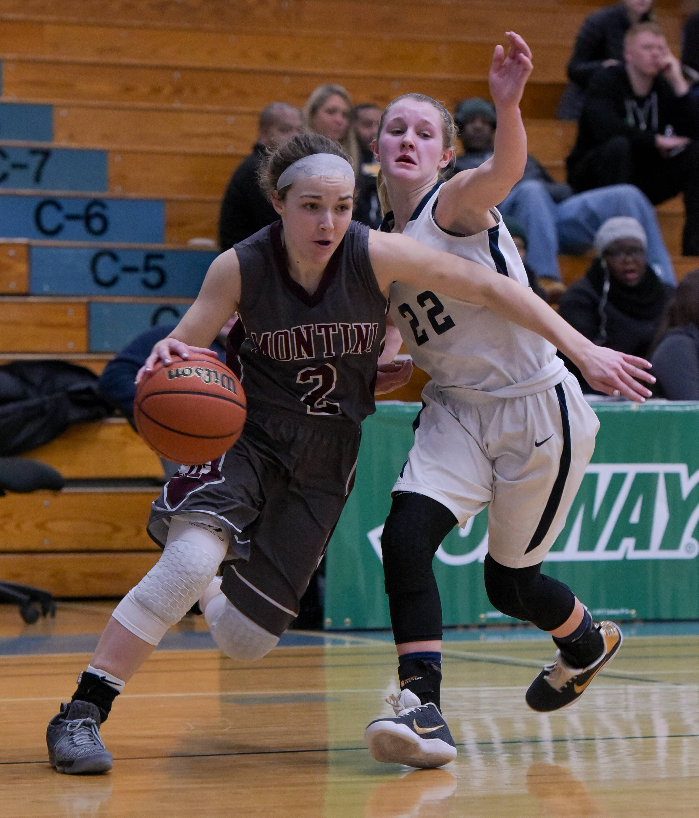 Montini's Sma Mitchell drives around Marquette Catholic's Morgan Crook during the Subway Classic girls basketball game on January 16, 2017.