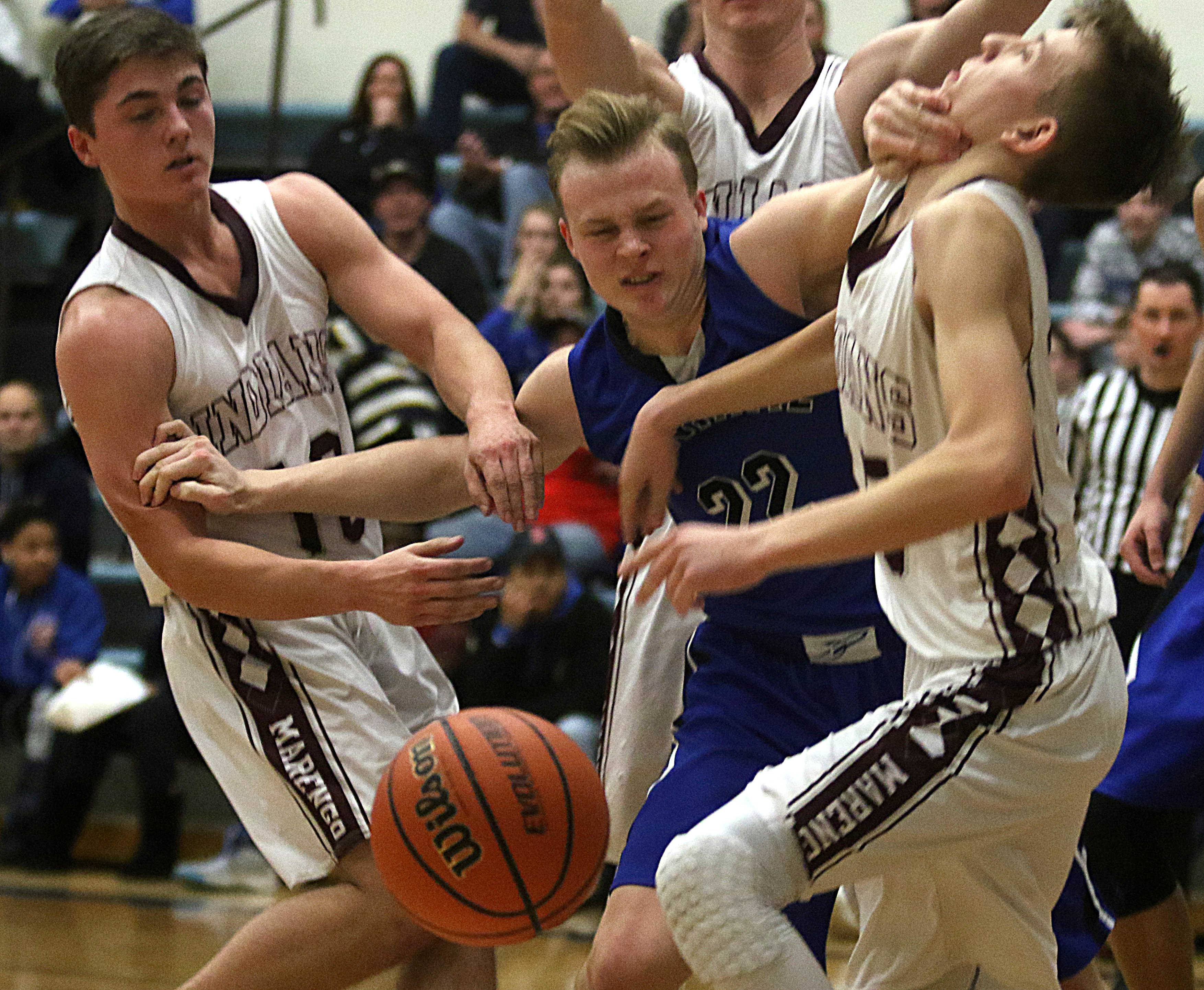 Burlington Central's Joey Ratzek, center, muscles his way through Marengo's Connor Wascher, left, and Aidan Kirchner, right, during the title game of the MLK Classic tournament at Burlington Monday night.